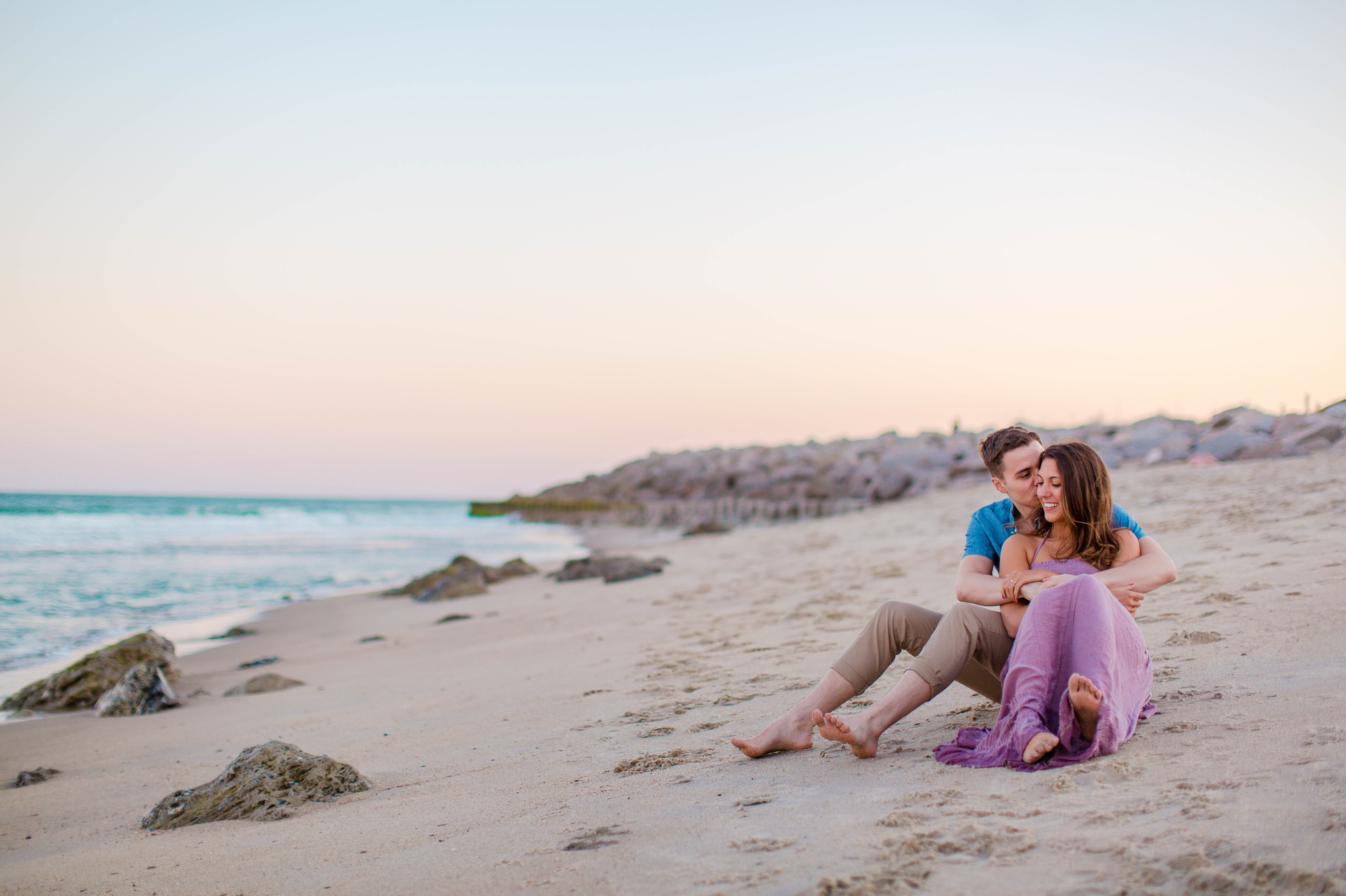 man and woman sitting in the sand - - Woman is in a flowy pastel maxi dress - candid and unposed golden light session - beach engagement photographer in honolulu, oahu, hawaii - johanna dye photography