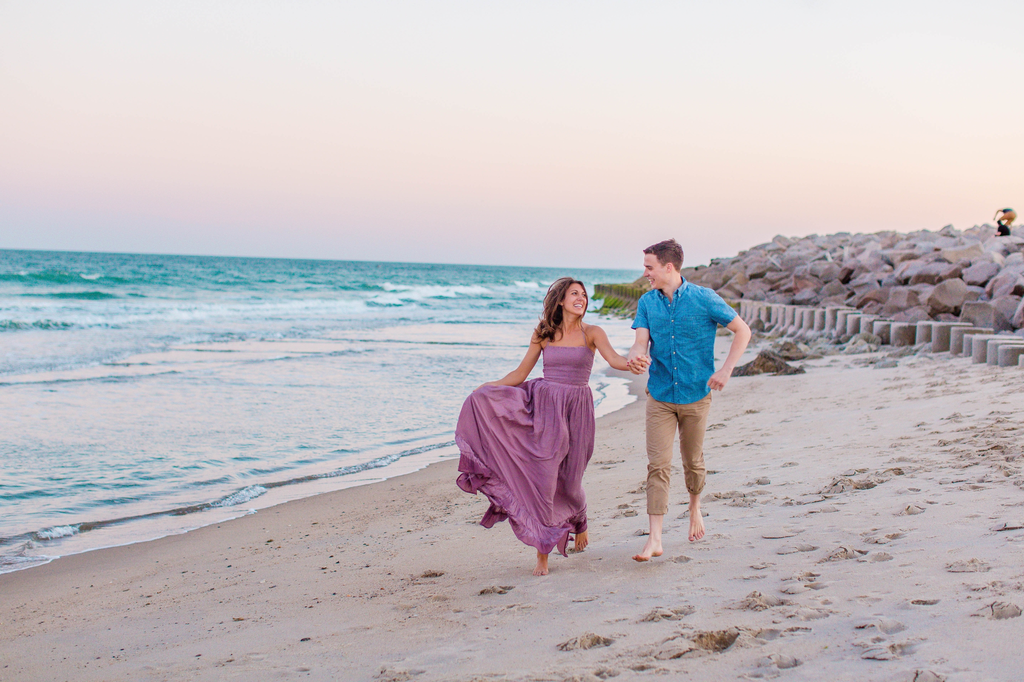 man and woman running in the sand - - Woman is in a flowy pastel maxi dress - candid and unposed golden light session - beach engagement photographer in honolulu, oahu, hawaii - johanna dye photography