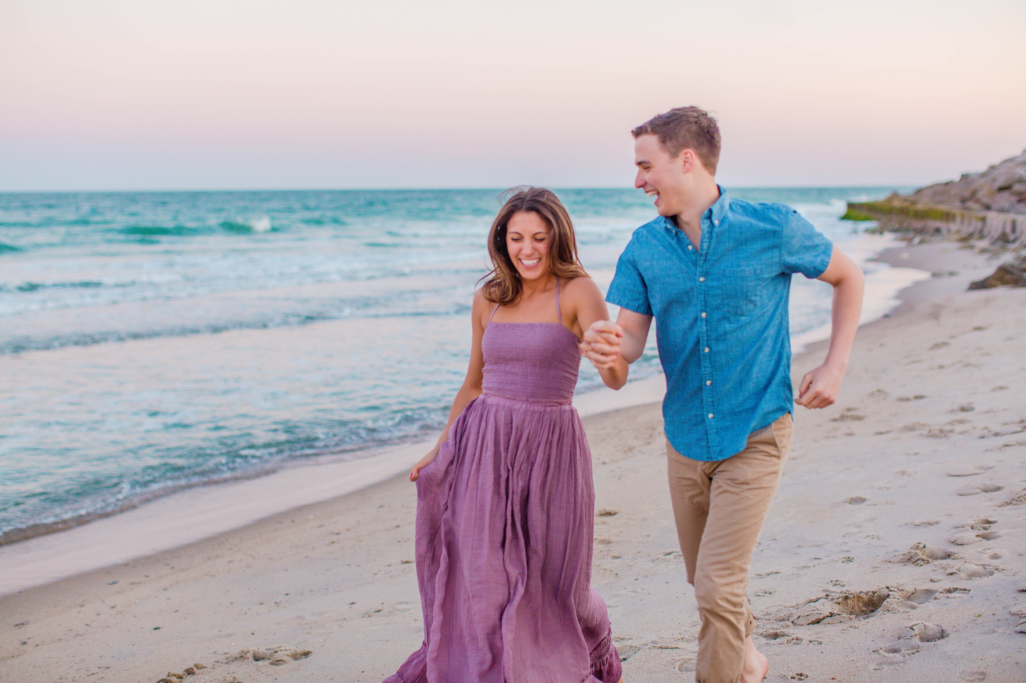 man and woman running on the beach and laughing - Woman is in a flowy pastel maxi dress - candid and unposed golden light session - beach engagement photographer in honolulu, oahu, hawaii - johanna dye photography