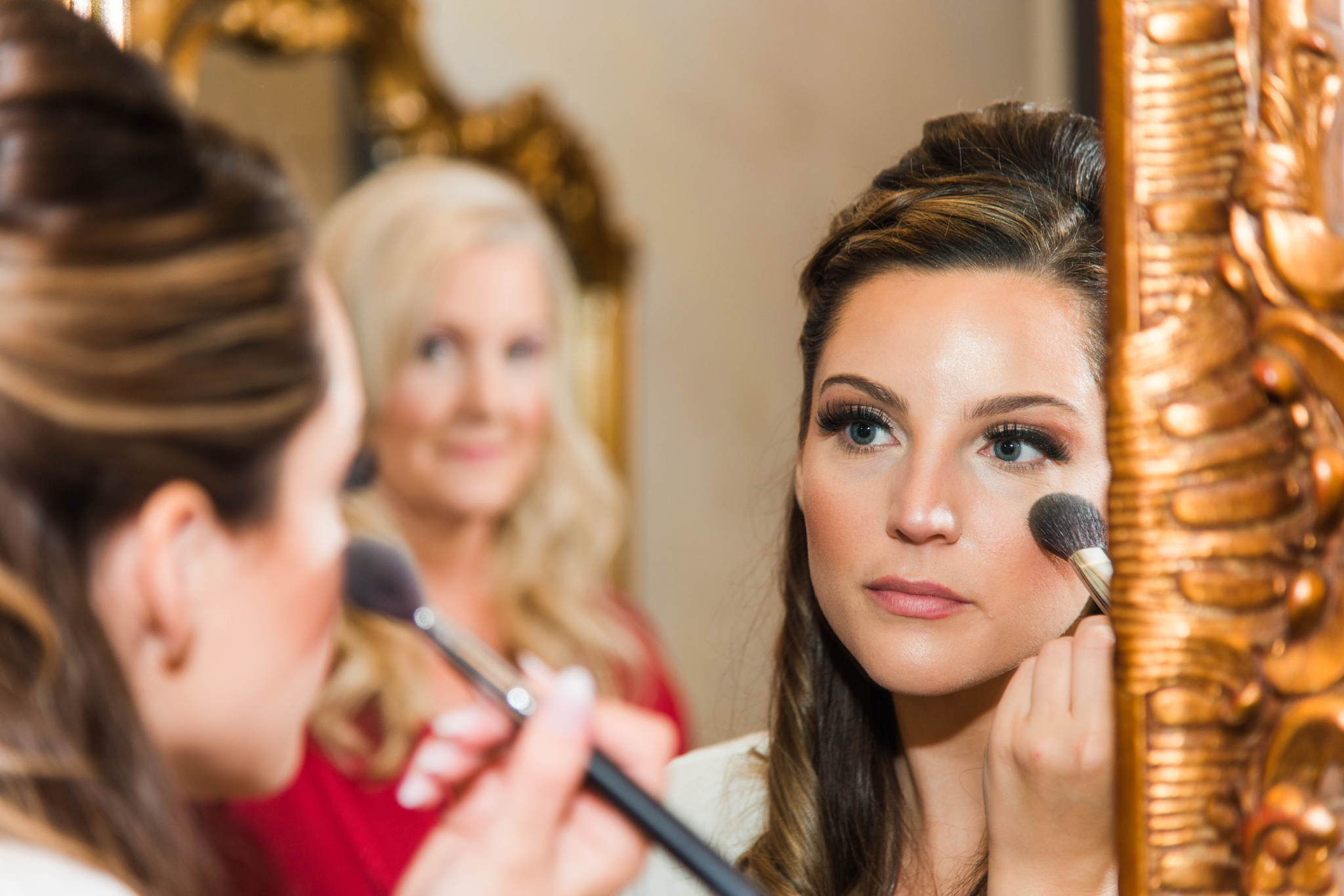 Bride putting on make up in the mirror while her mother is smiling at her - Honolulu Oahu Hawaii Wedding Photographer