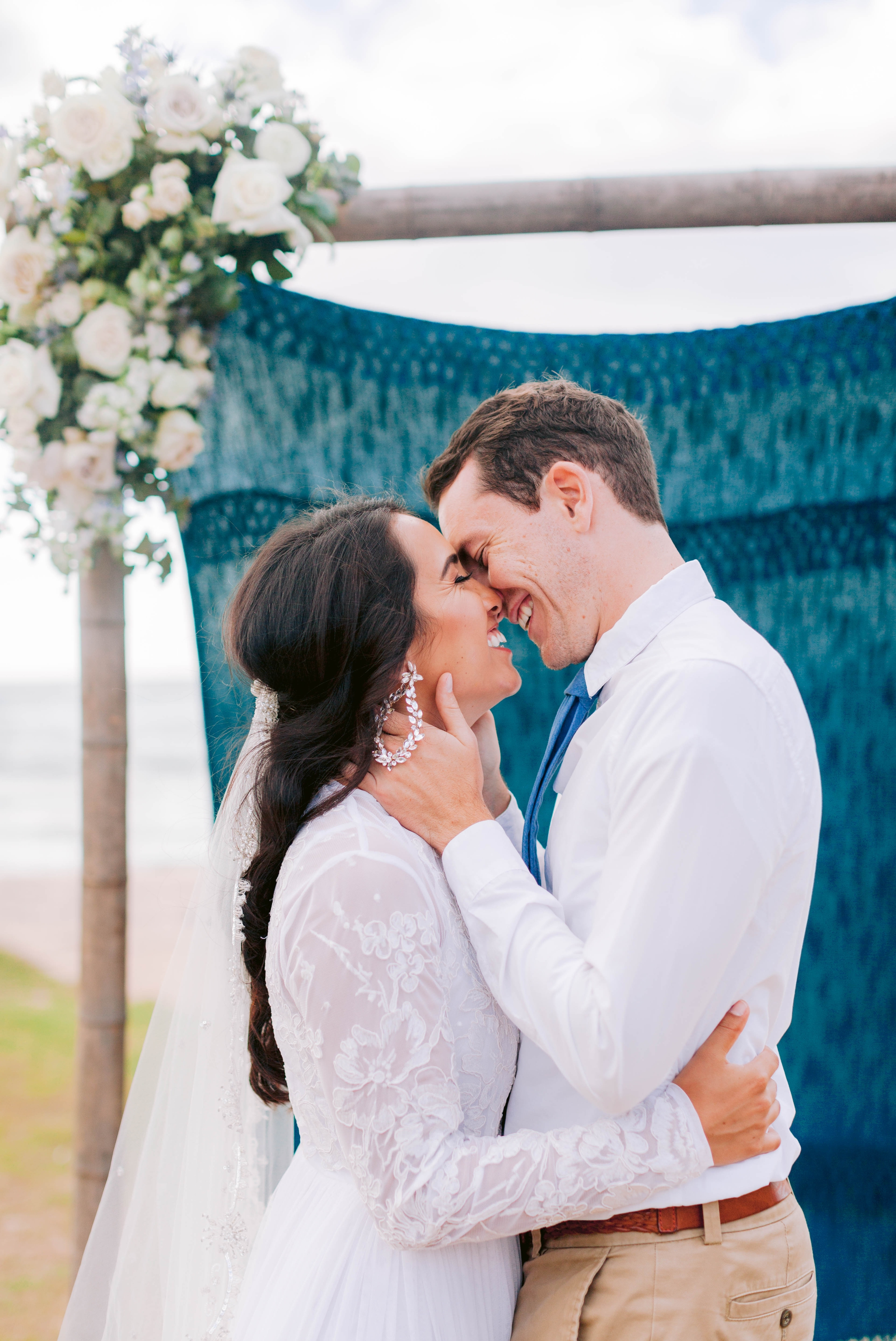 Bride + Groom kissing in front of a ceremony arch decorated with fabric and flowers - Ana + Elijah - Wedding at Loulu Palm in Haleiwa, HI - Oahu Hawaii Wedding Photographer