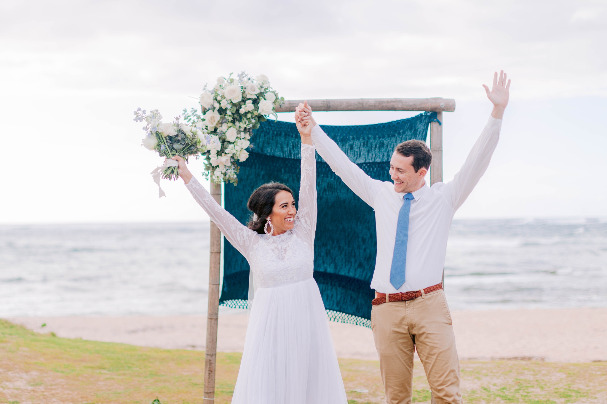 Bride and Groom cheering at the ceremony at the beach - Ana + Elijah - Wedding at Loulu Palm in Haleiwa, HI - Oahu Hawaii Wedding Photographer