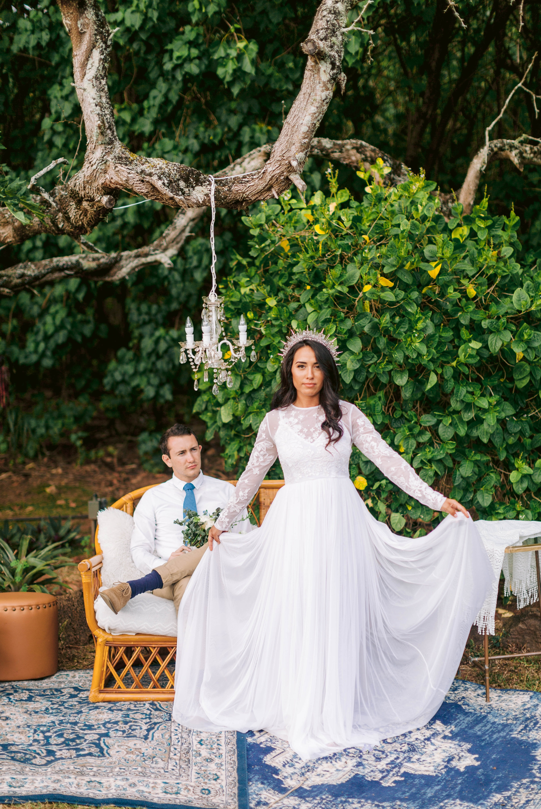 Bride and groom relaxing in an outdoor lounge with rattan furniture and blue rugs -  bride is wearing a wedding dress by asos and a crystal crown - Ana + Elijah - Wedding at Loulu Palm in Haleiwa, HI - Oahu Hawaii Wedding Photographer