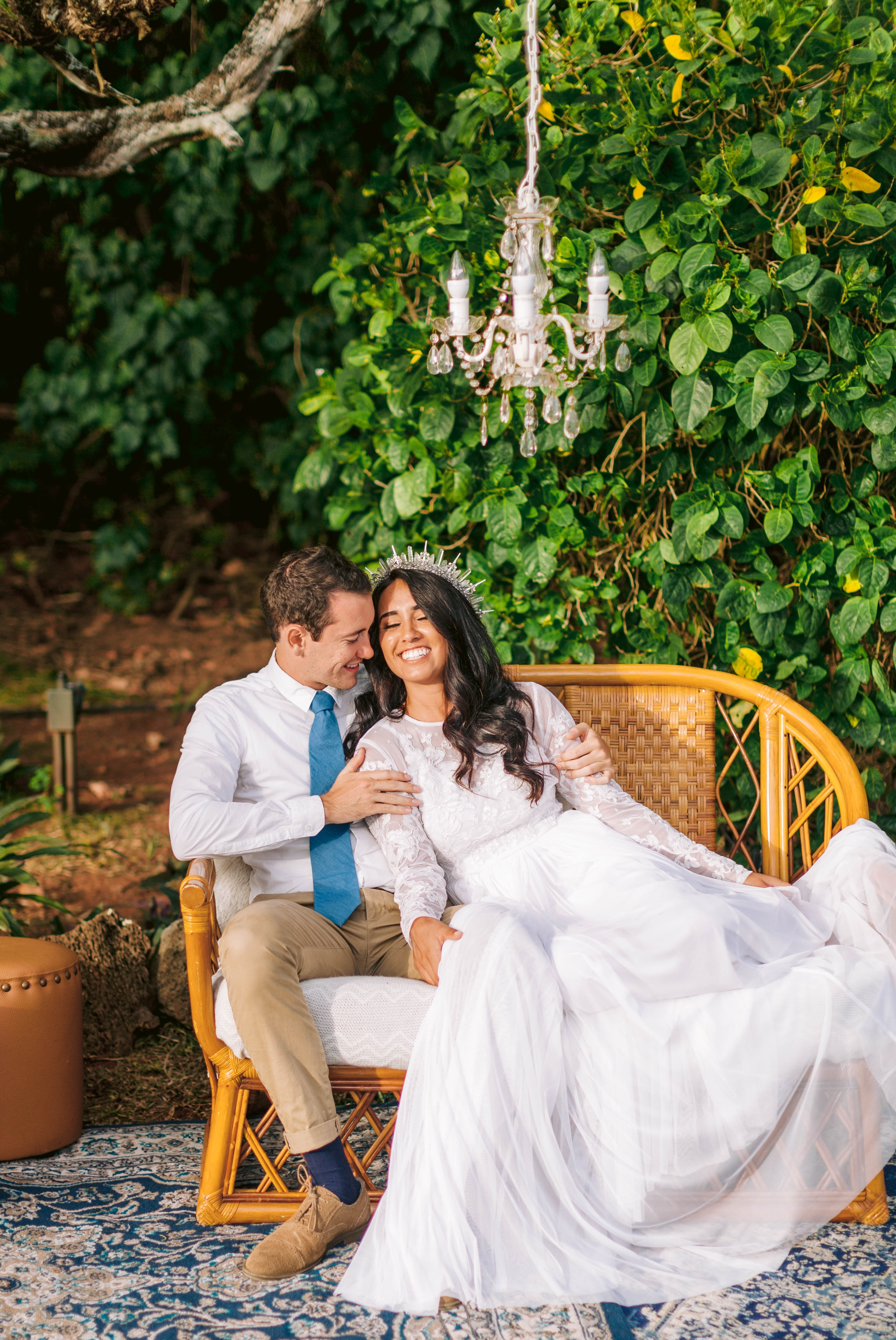 Bride and groom cuddeling an outdoor lounge - white dress by asos - unique crystal crown Ana + Elijah - Wedding at Loulu Palm in Haleiwa, HI - Oahu Hawaii Wedding Photographer - #hawaiiweddingphotographer #oahuweddings #hawaiiweddings