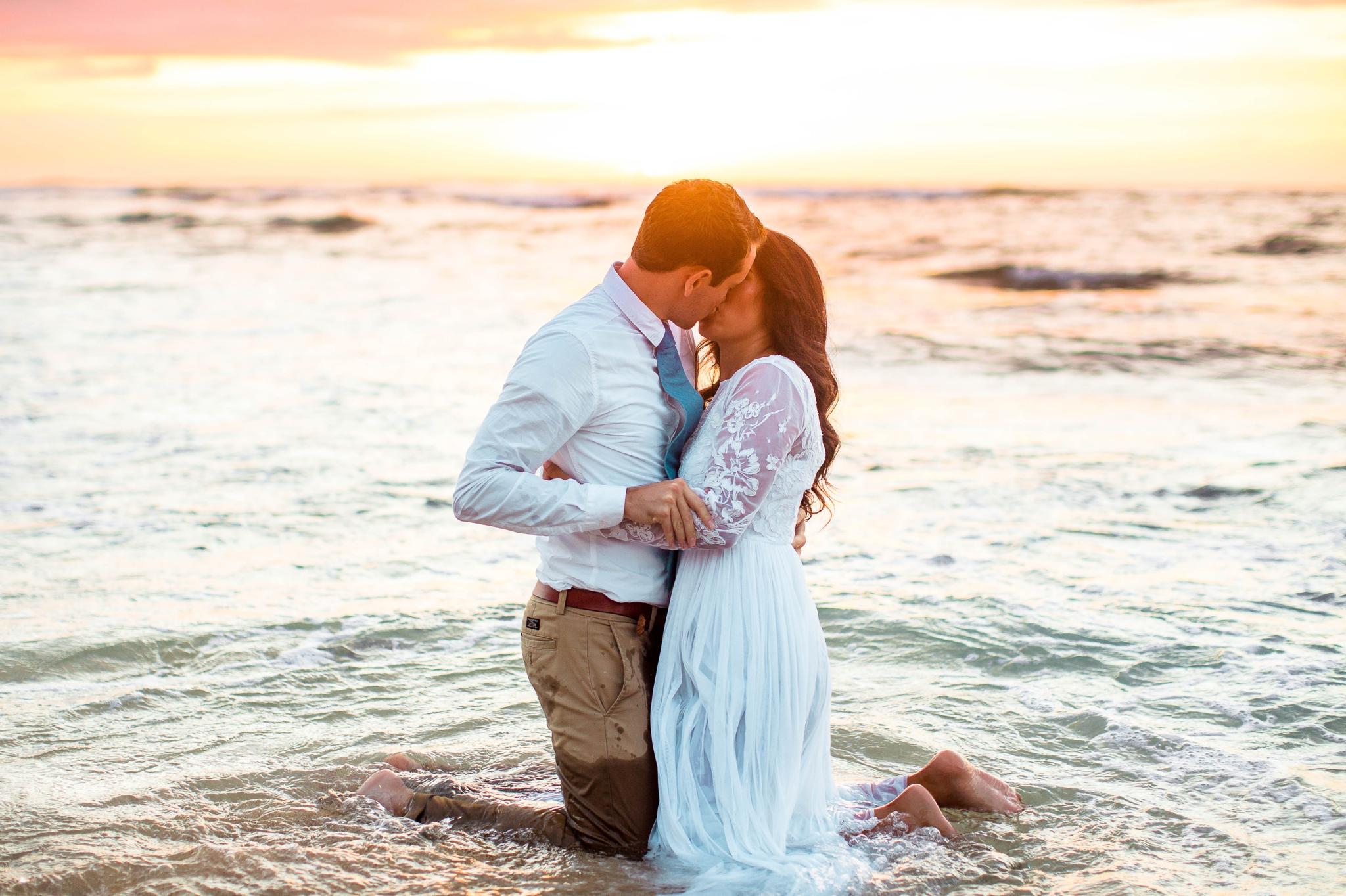 Bride and Groom kissing in the ocean - Wedding Portraits at Sunset in Hawaii - Ana + Elijah - Wedding at Loulu Palm in Haleiwa, HI - Oahu Hawaii Wedding Photographer - #hawaiiweddingphotographer #oahuweddings #hawaiiweddings