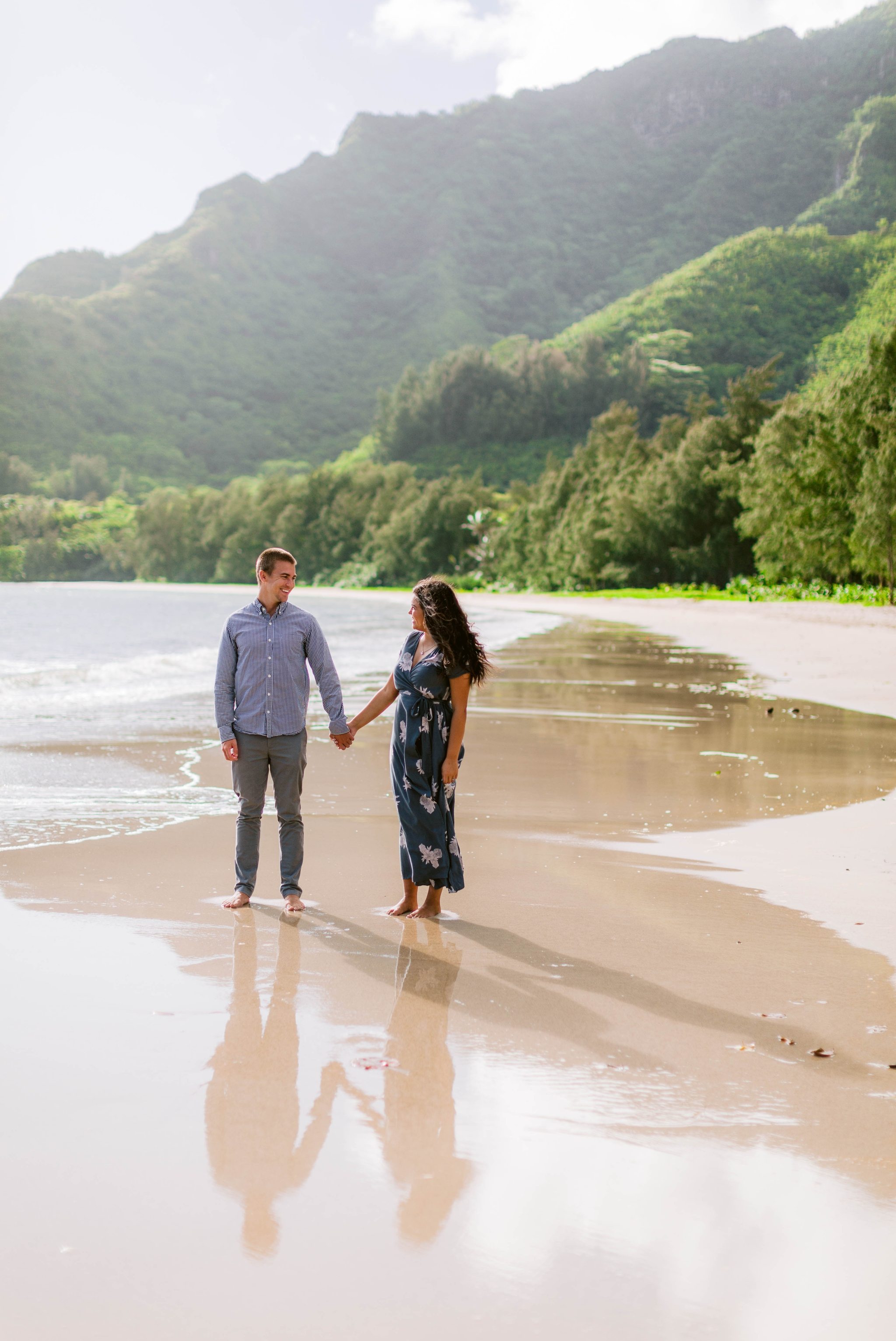 Couple at the shore with their reflections in the sand - Rilee + Max - Beach Engagement Session at Kahana Bay in Kaaawa, HI - Oahu Hawaii Wedding Photographer - #hawaiiengagementphotographer #oahuengagementphotographer