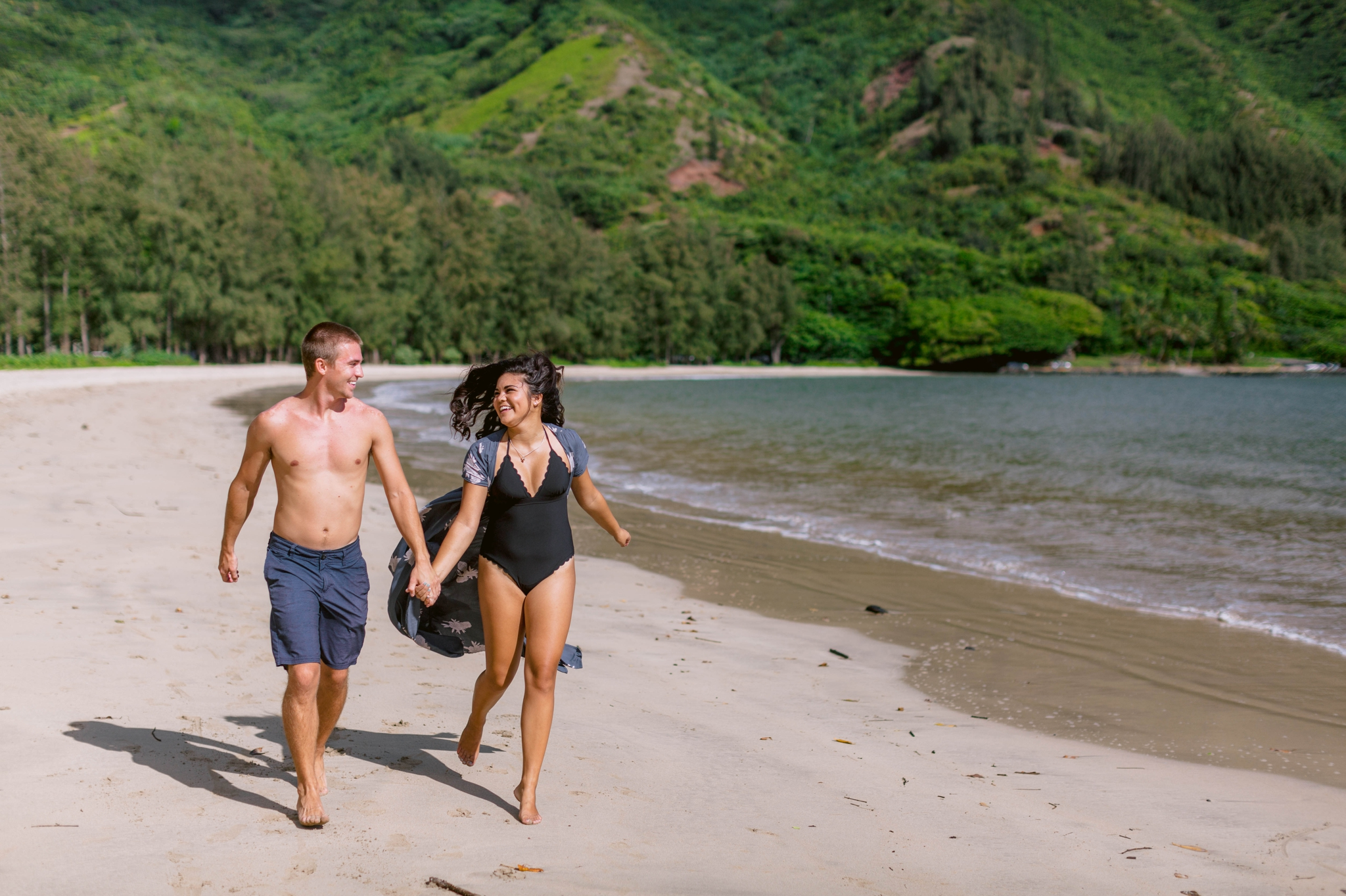 Couple running in their bathing suits - Rilee + Max - Beach Engagement Session at Kahana Bay in Kaaawa, HI - Oahu Hawaii Wedding Photographer - #hawaiiengagementphotographer #oahuengagementphotographer