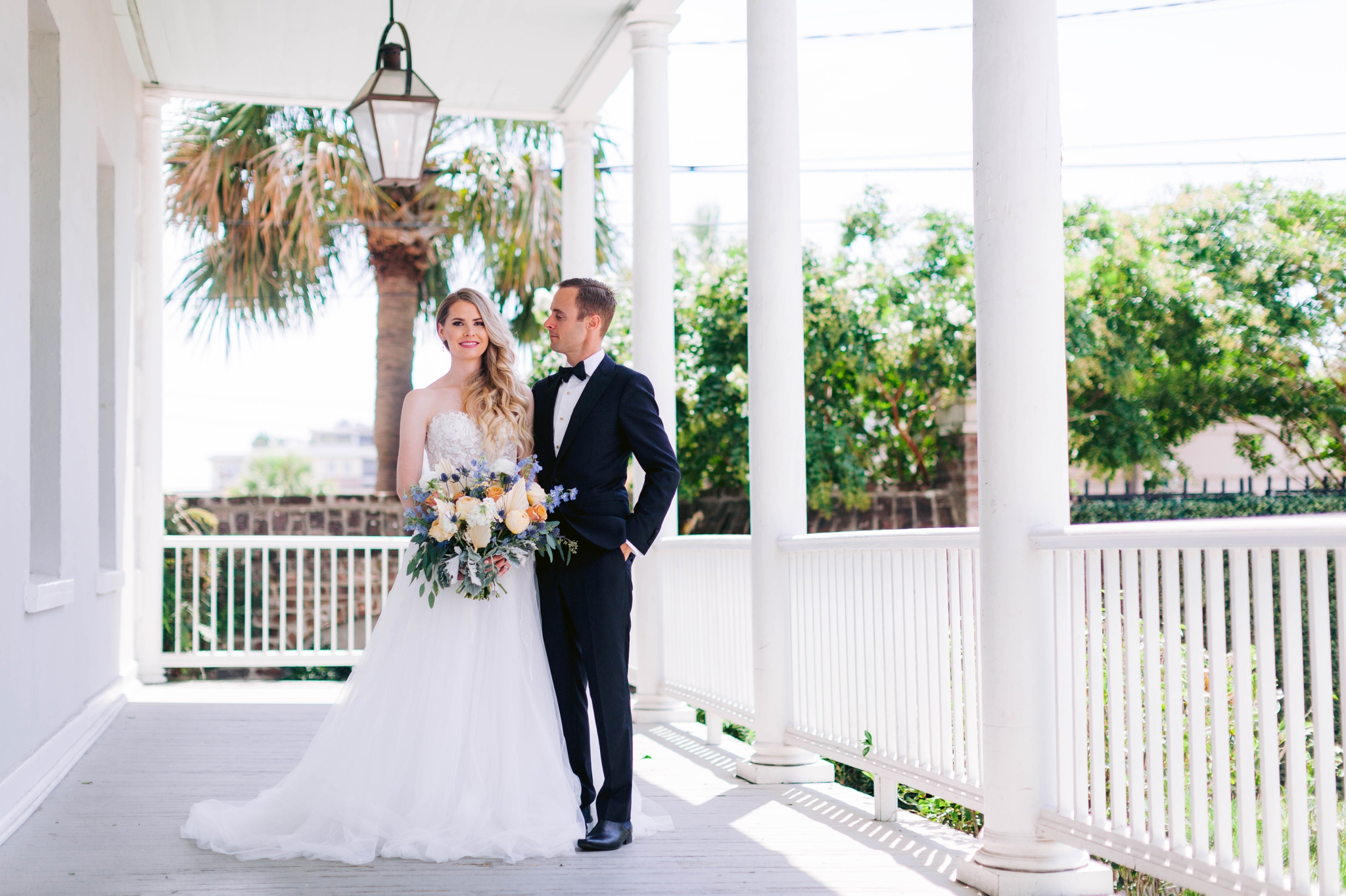 - Bride and Groom Fine art natural light photography - black tucks and a ballgown wedding dress on a white porch with palm trees in the background  - martha stewart weddings - style me pretty - Dusty Blue Wedding Inspiration - fine art photography - Honolulu, Oahu, Hawaii Wedding Photographer - johanna dye