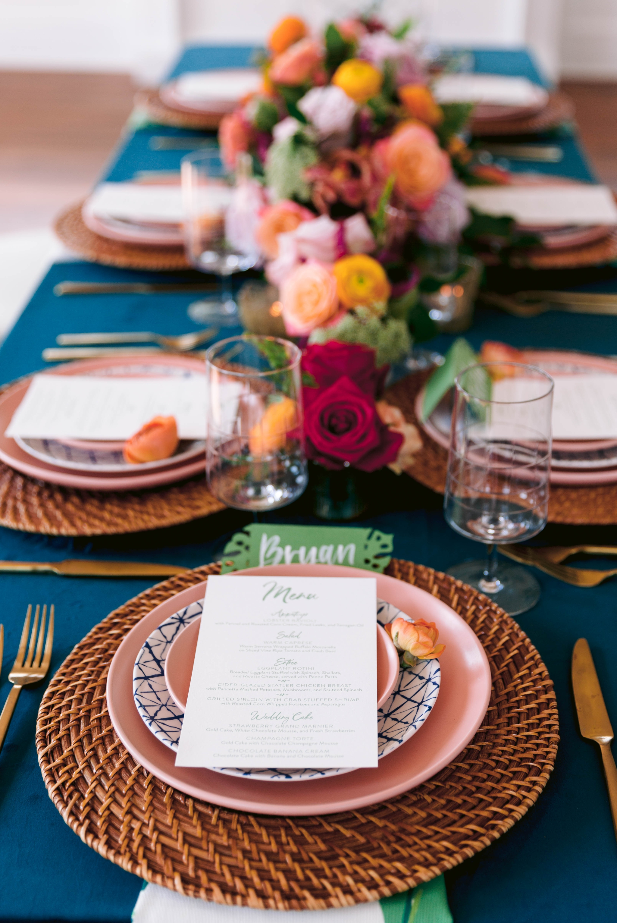Table Setting with a gorgeous colorful flower arrangement, blush and blue plates with gold flatware and a tropical name card as well as a calligraphy menu - Navy, Green, Gold and Berry colored Tropical Wedding Inspiration for your Wedding in Hawaii! - Honolulu, Oahu, Hawaii Photographer
