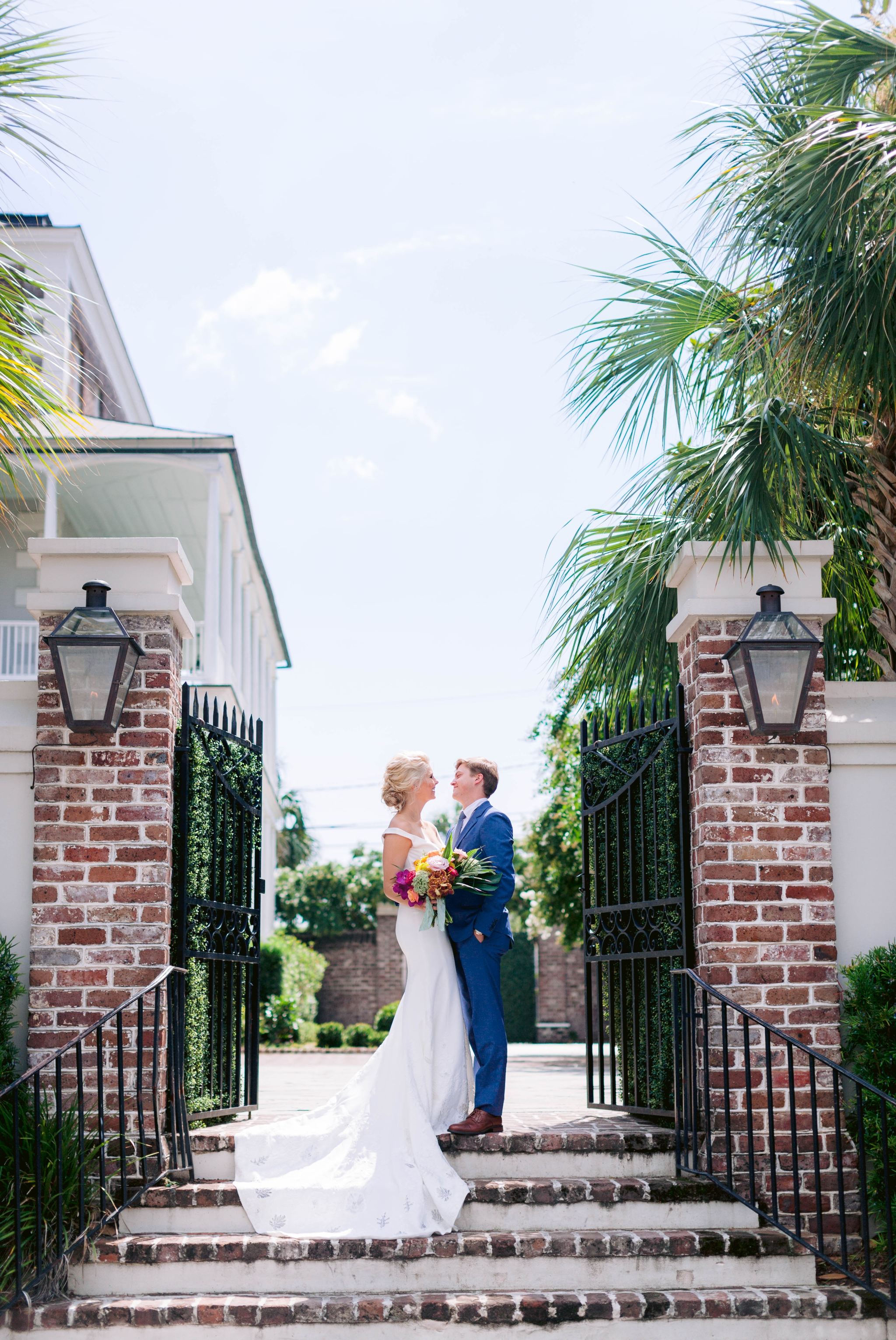 Bride and Groom Portraits at the gorgeous entry gate with palm trees in the background - Navy, Green, Gold and Berry colored Tropical Wedding Inspiration for your Wedding in Hawaii! - Honolulu, Oahu, Hawaii Photographer - Fine Art Film Photography - Light and Airy