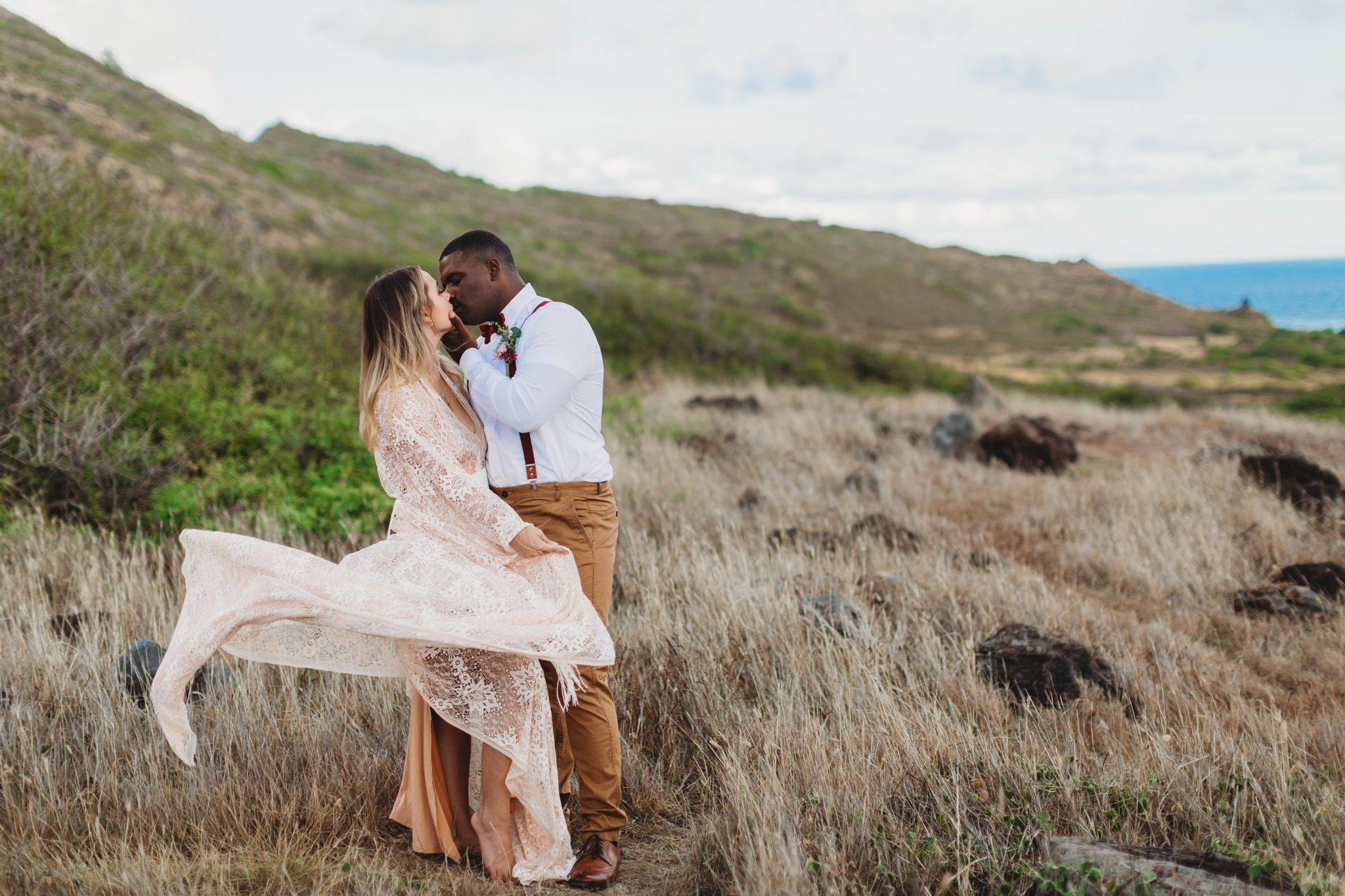 Elopement at Makapuu Lookout, Waimanalo, HI - Oahu Hawaii Engagement Photographer - Bride in a flowy fringe boho wedding dress - in grassy mountains with the ocean in the back - lanikai lookout - deutsche hochzeits fotografin in hawaii