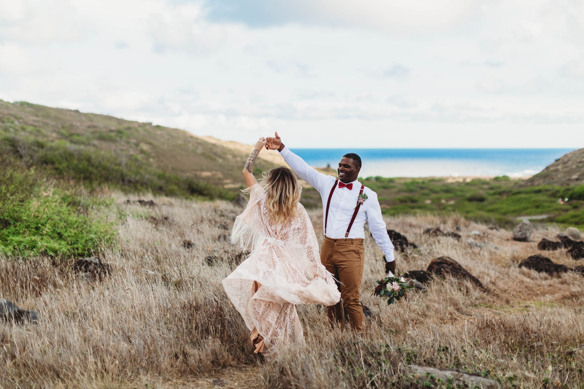 Elopement at Makapuu Lookout, Waimanalo, HI - Oahu Hawaii Engagement Photographer - Bride in a flowy fringe boho wedding dress - in grassy mountains with the ocean in the back - couple is dancing and the dress is blowing in the wind - lanikai lookout - deutsche hochzeits fotografin in hawaii