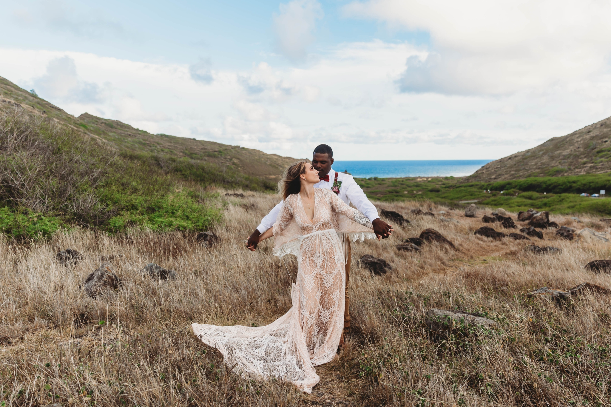 couple dancing around in the wind - Elopement at Makapuu Lookout, Waimanalo, HI - Oahu Hawaii Engagement Photographer - Bride in a flowy fringe boho wedding dress - in grassy mountains with the ocean in the back - lanikai lookout - deutsche hochzeits fotografin in hawaii - smal1 - dark and moody - true to live