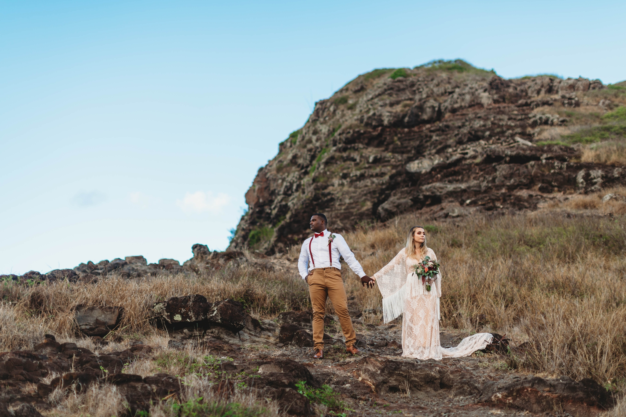 couple standing besides the cliffs - Elopement at Makapuu Lookout, Waimanalo, HI - Oahu Hawaii Engagement Photographer - Bride in a flowy fringe boho wedding dress - in grassy mountains with the ocean in the back - lanikai lookout - deutsche hochzeits fotografin in hawaii - smal1 - dark and moody - true to live