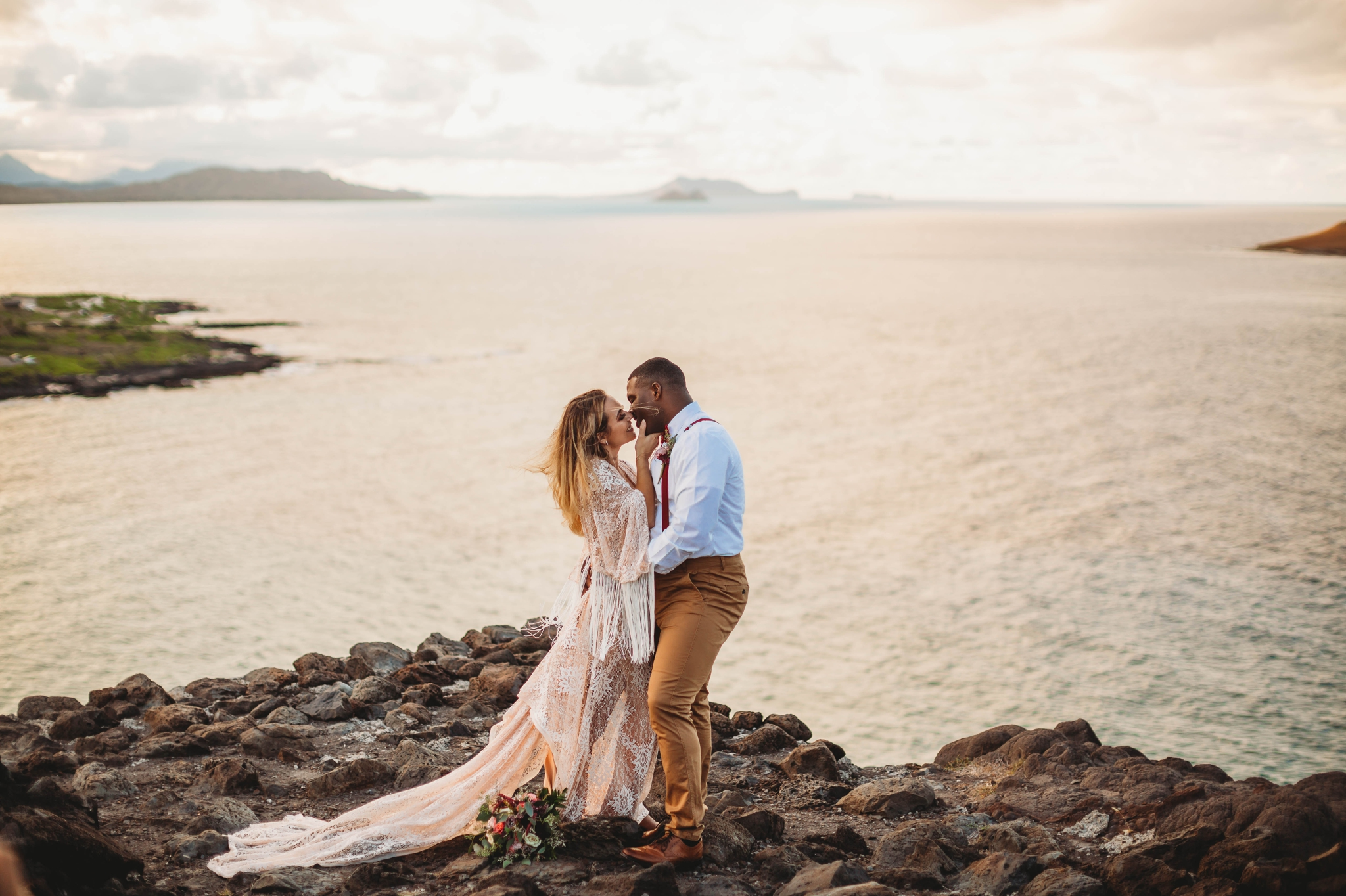 couple on the cliffs above Makapuu Beach at the Lookout, Waimanalo, HI - Oahu Hawaii Engagement Photographer - Bride in a flowy fringe boho wedding dress - lanikai lookout - deutsche hochzeits fotografin in hawaii - smal1 - dark and moody - true to live
