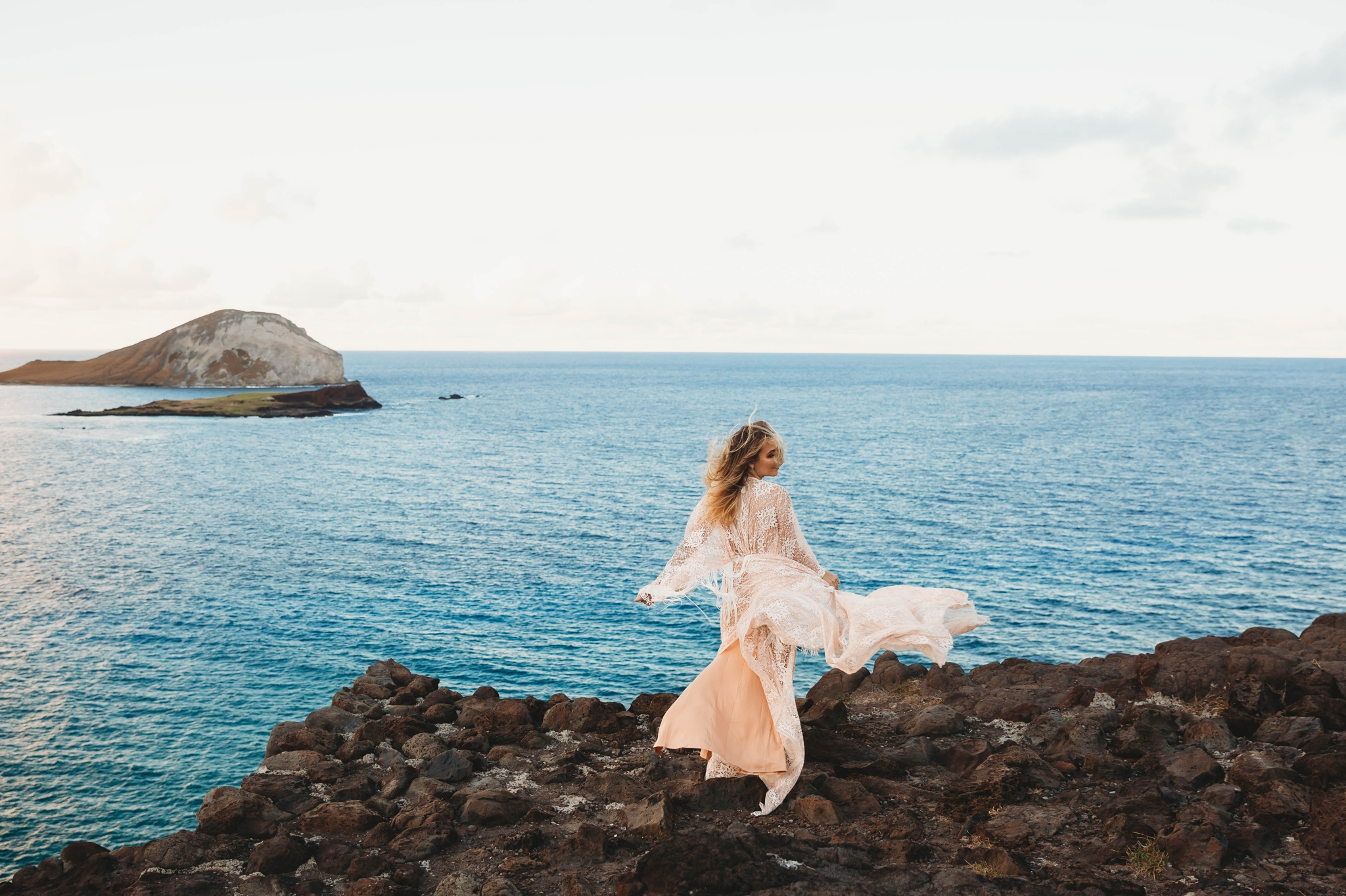 Bride in a flowy fringe boho wedding dress on the cliffs above Makapuu Beach at the Lookout, Waimanalo, HI looking over the ocean with the  Kāohikaipu Island in the background  - Oahu Hawaii Engagement Photographer - lanikai lookout - deutsche hochzeits fotografin in hawaii - smal1 - dark and moody - true to live