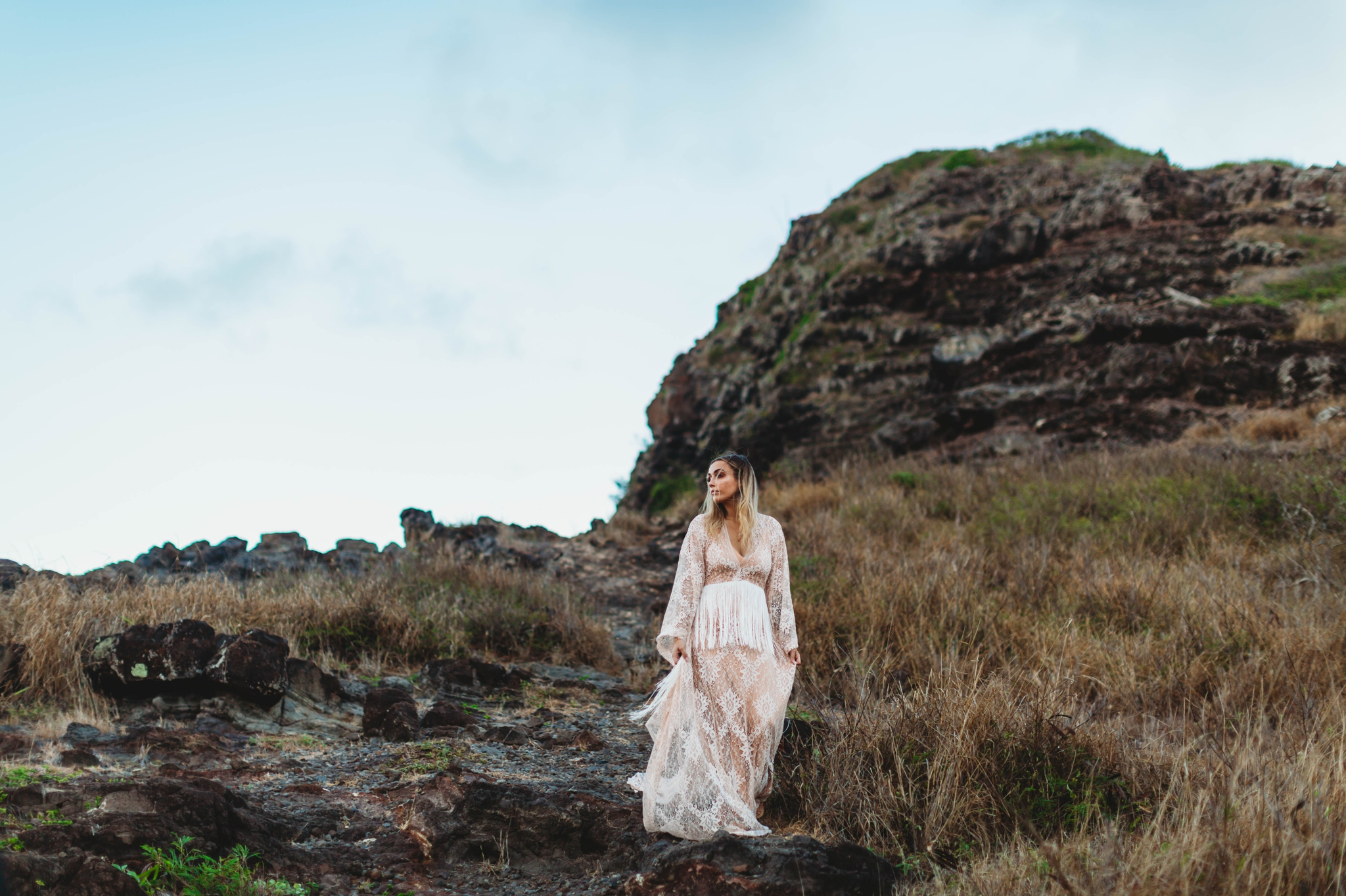 bride standing on top of a mountain - Elopement at Makapuu Lookout, Waimanalo, HI - Oahu Hawaii Engagement Photographer - Bride in a flowy fringe boho wedding dress - lanikai lookout - deutsche hochzeits fotografin in hawaii - smal1 - dark and moody - true to live