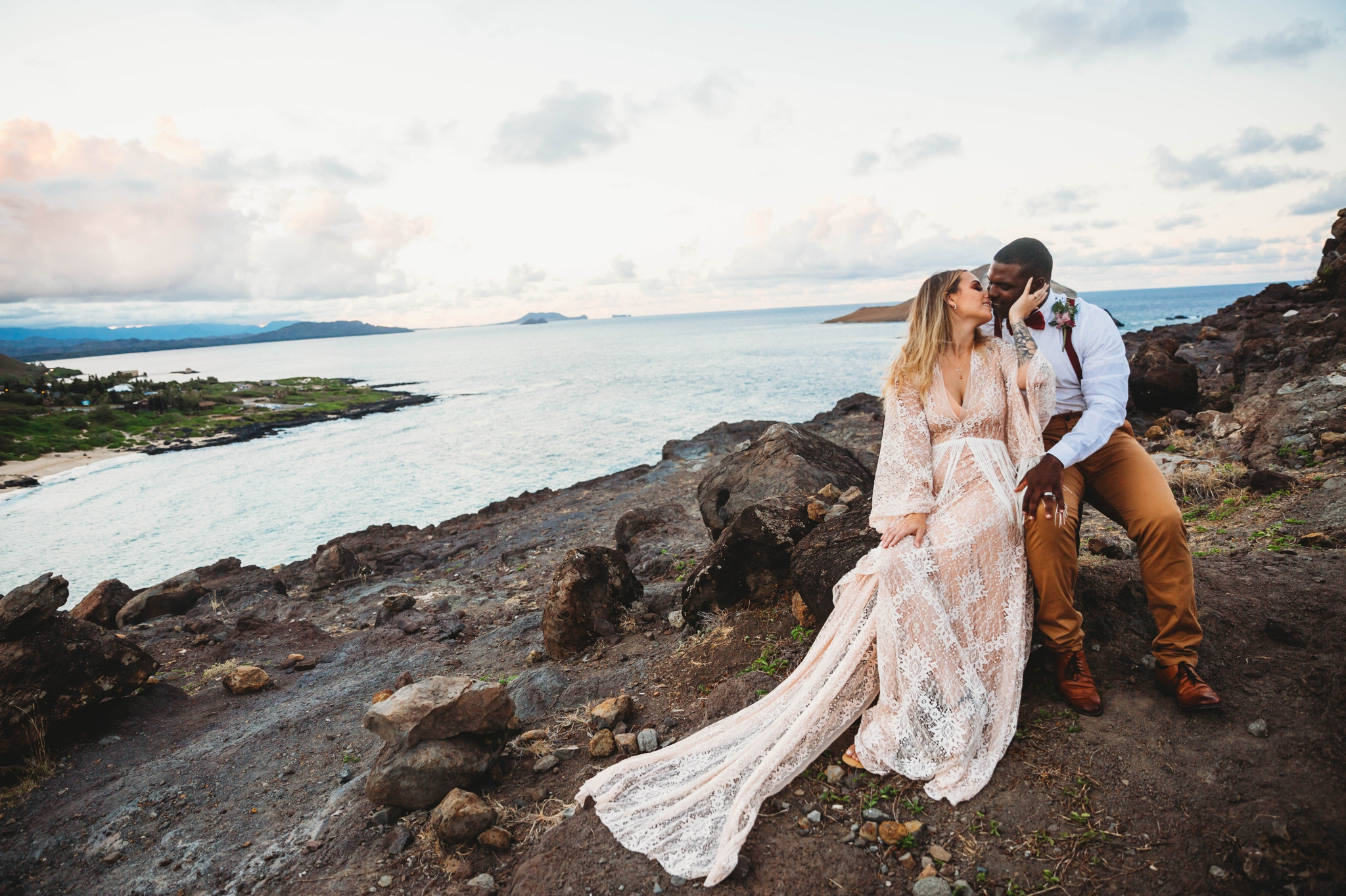 couple kissing on the cliffs above Makapuu Beach at the Lookout, Waimanalo, HI - Oahu Hawaii Engagement Photographer - Bride in a flowy fringe boho wedding dress - lanikai lookout - deutsche hochzeits fotografin in hawaii - smal1 - dark and moody - true to live