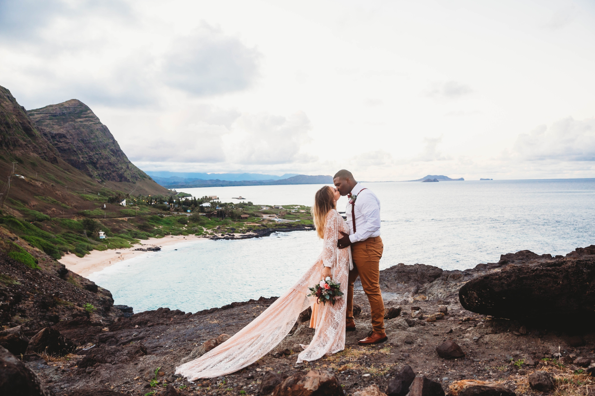first kiss between bride and groom - wedding ceremony at Makapuu Lookout overlooking the ocean and beach, Waimanalo, HI - Oahu Hawaii Engagement Photographer - Bride in a flowy fringe boho wedding dress - lanikai lookout - deutsche hochzeits fotografin in hawaii - smal1 - dark and moody - true to live