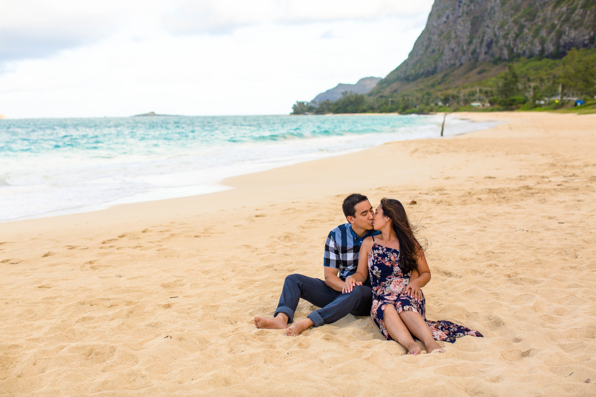 engagement photography session at waimanalo beach park - couple is sitting in the sand with the ocean and the mountains in the back ground - oahu hawaii wedding photographer