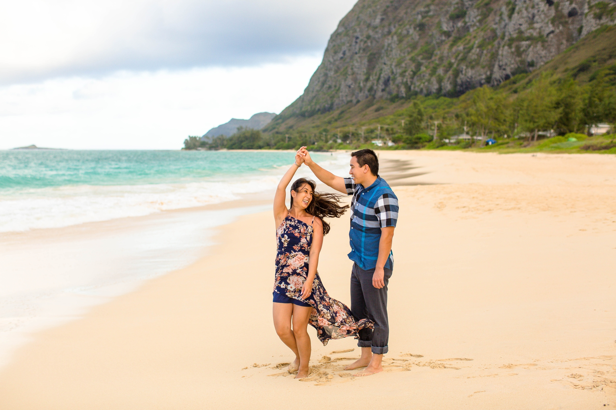 engagement photography session at waimanalo beach park - couple is dancing and twirling in the sand with the ocean and the mountains in the back ground - oahu hawaii wedding photographer
