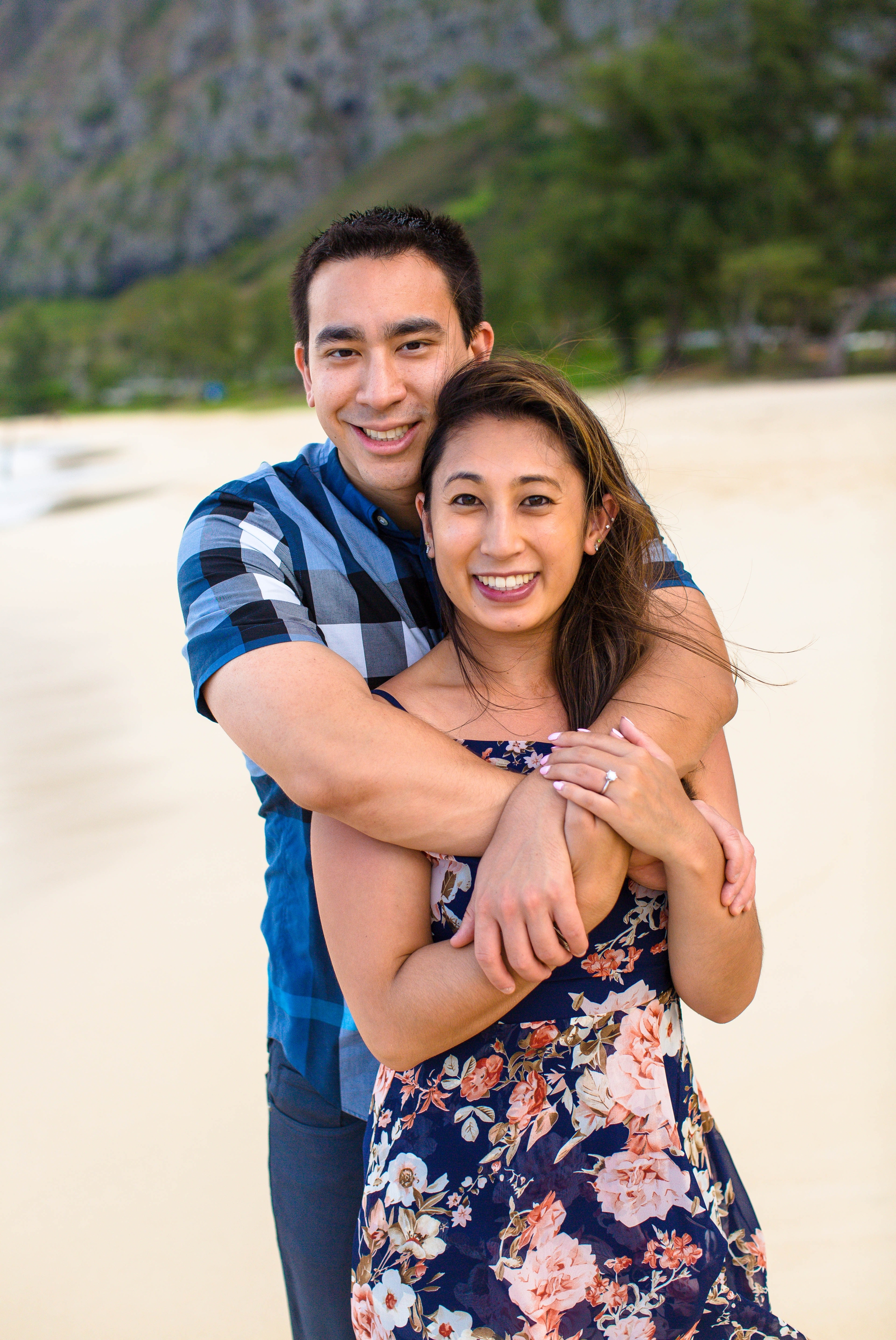 engagement photography session at waimanalo beach park - couple is kissing and snuggeling up to each other in the sand with the ocean and the mountains in the back ground - oahu hawaii wedding photographer