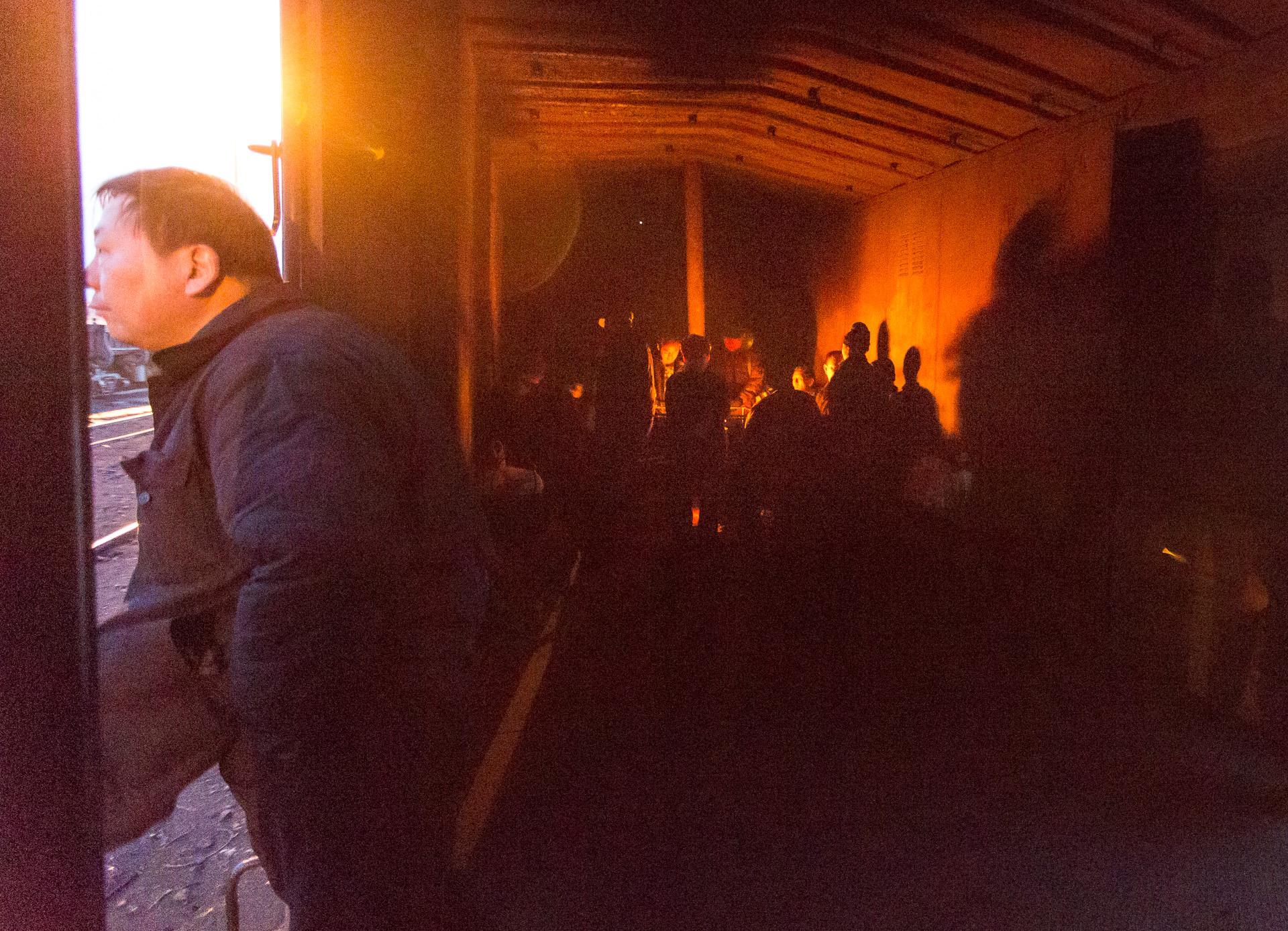 Arbeiter auf dem Weg zum Schichtwechsel. Während draußen die Sonne aufgeht wärmen sie sich bei Minusgraden im Güterwagen am Kanonenofen.