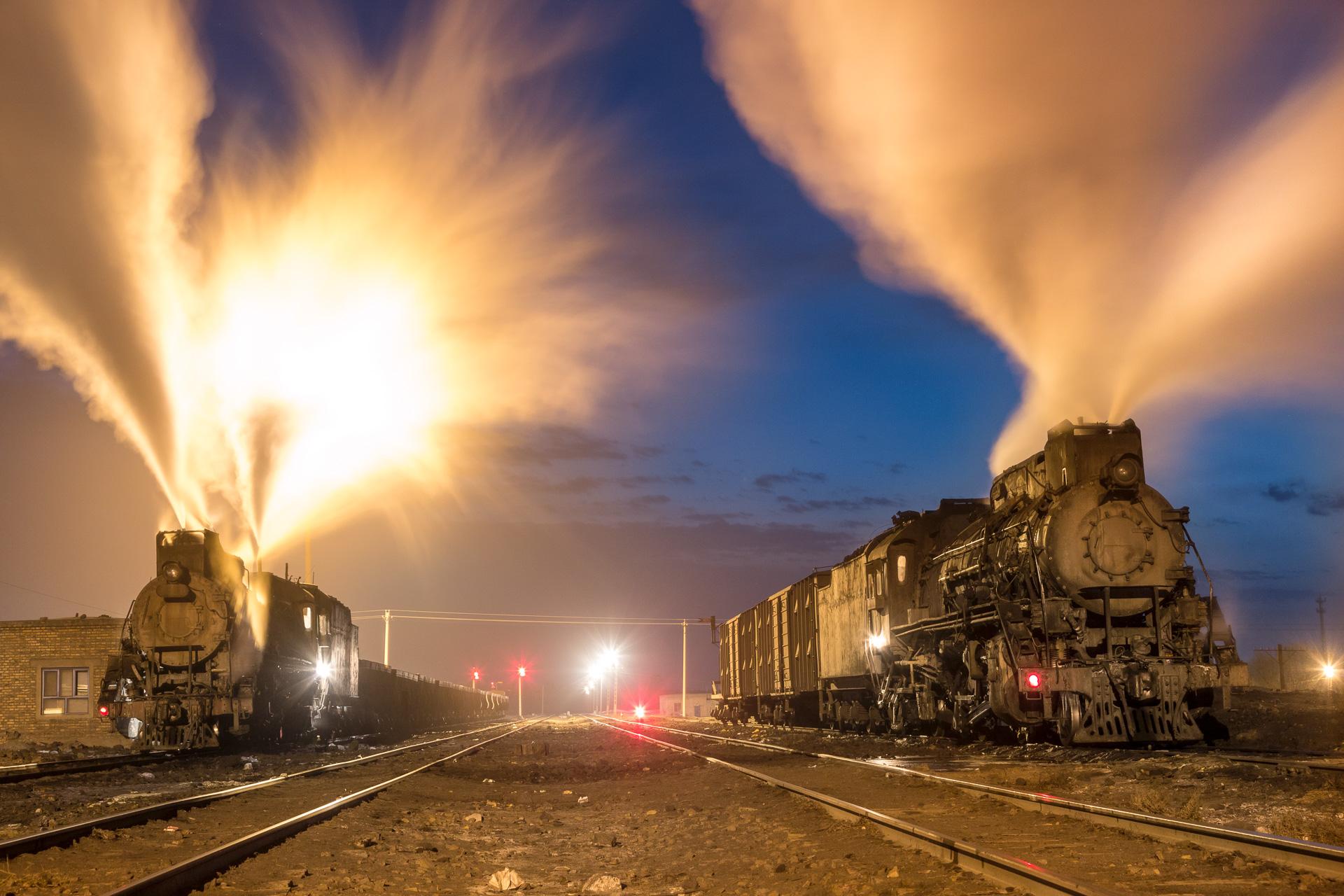 Vor Sonnenaufgang treffen sich zwei Lokomotiven der  JS  Klasse in Dongbolizhan, Provinz Xinjiang. Die Dezemberkälte von minus 20 Grad lässt die Dampfwolken weit in den Himmel steigen.