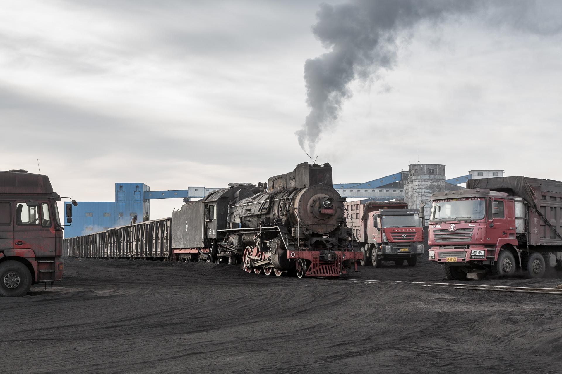 """LKWs bedrängen die """"alte"""" Dampflok"""