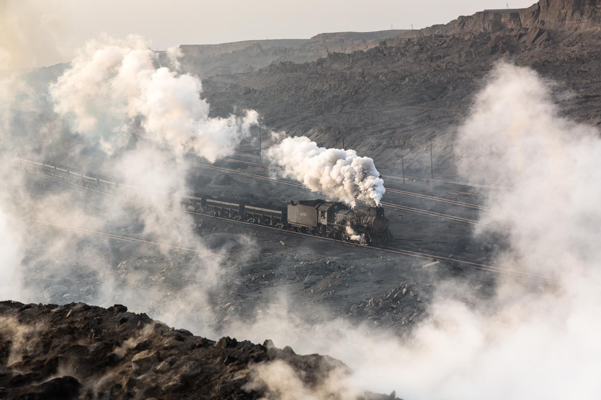 im Vordergrund: Kohleflöze brennen unter der geschundenen Oberfläche