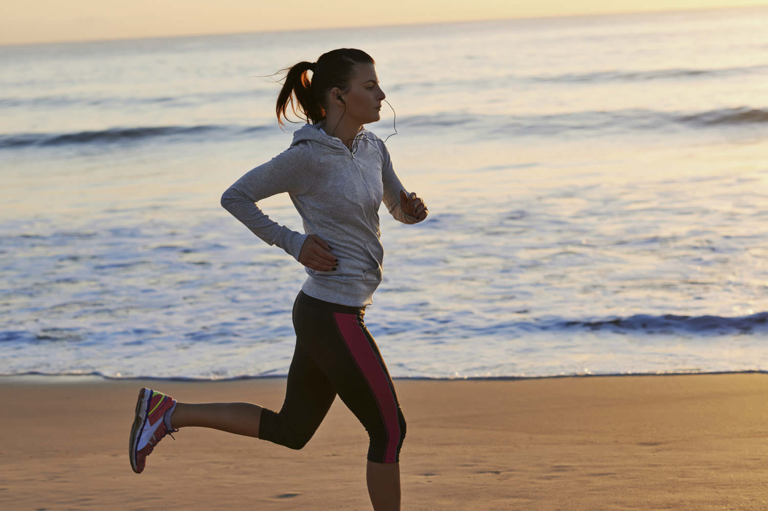 Runner listening to flashcards while jogging on beach