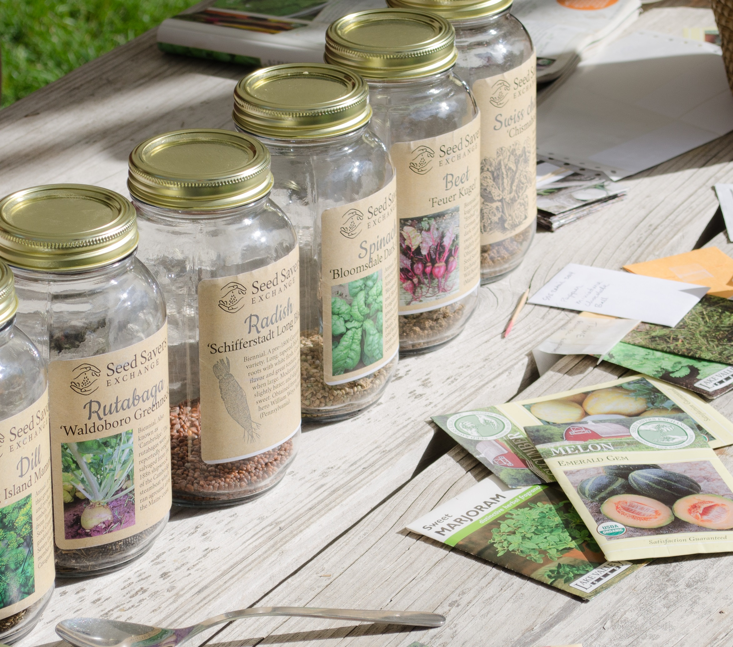 Packets and mason jars are among the containers used to display seeds at seed swaps. Plastic BagGies work well too.