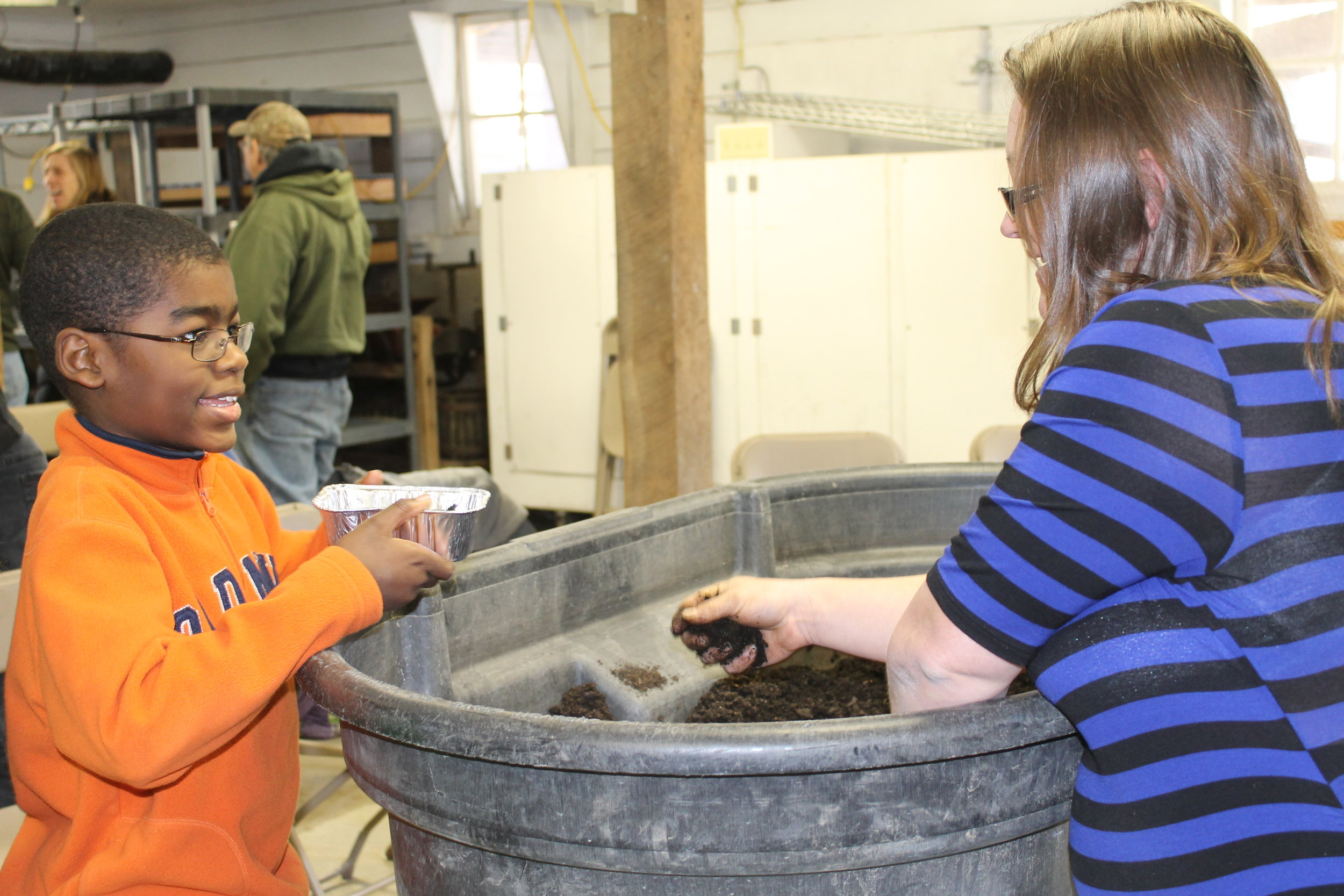 "Heidi Hackman shares soil with a young attendee of the 2017 ""Start with a Seed"" workshop. The 2018 workshop will be held March 3 at Heritage Farm in Decorah."