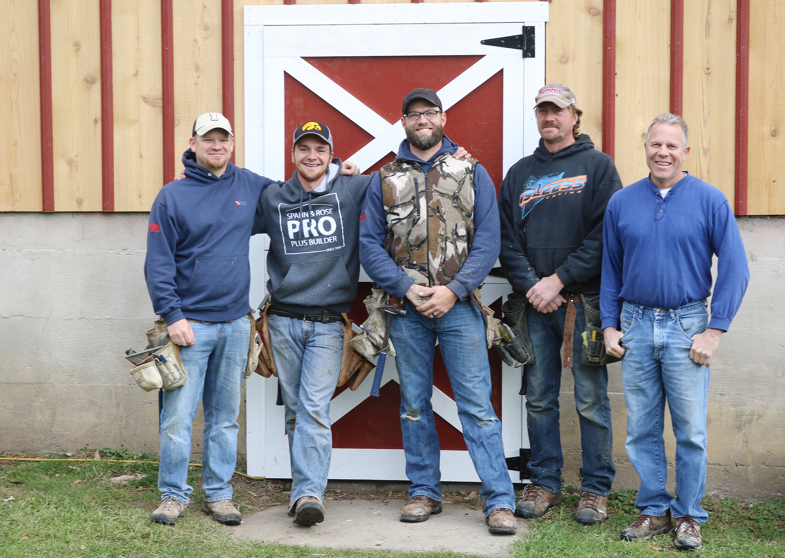 Steve Munkel (far right), owner of Munkel Construction, poses with his crew outside the barn at Heritage Farm in October.