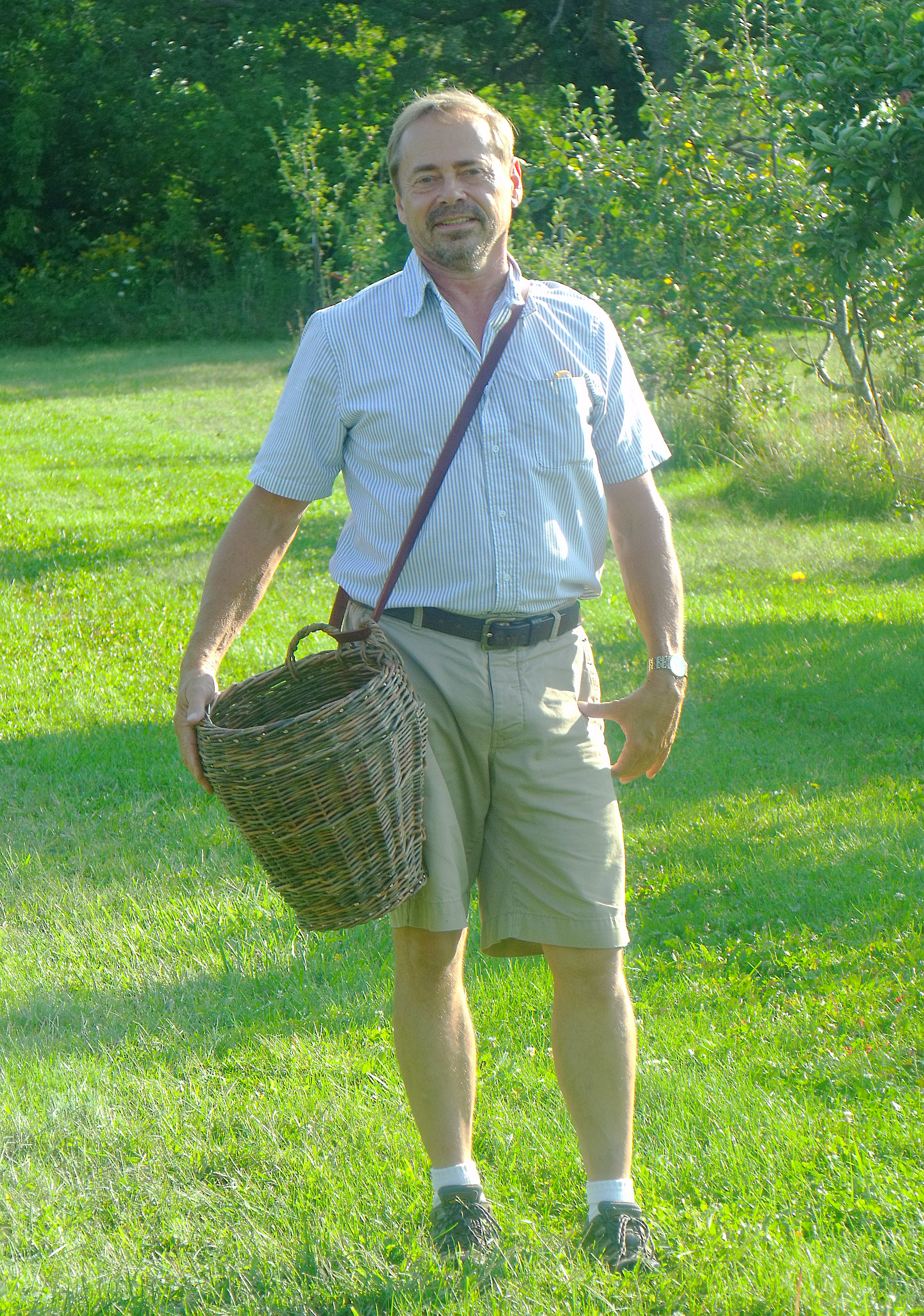 Dan Bussey, former Seed Savers Exchange orchard manager and advisor, collects apples in the Historic Orchard at Heritage Farm. Bussey maintained and grew the orchard collection during his years overseeing orchard operations.