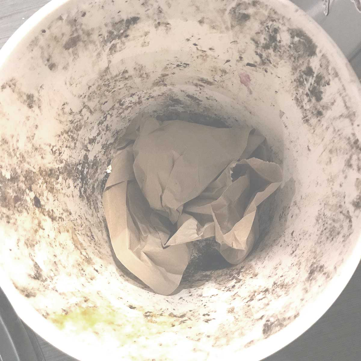 Bennett Compost suggested using crumpled up paper at the bottom of the bucket to make it easier to clean out