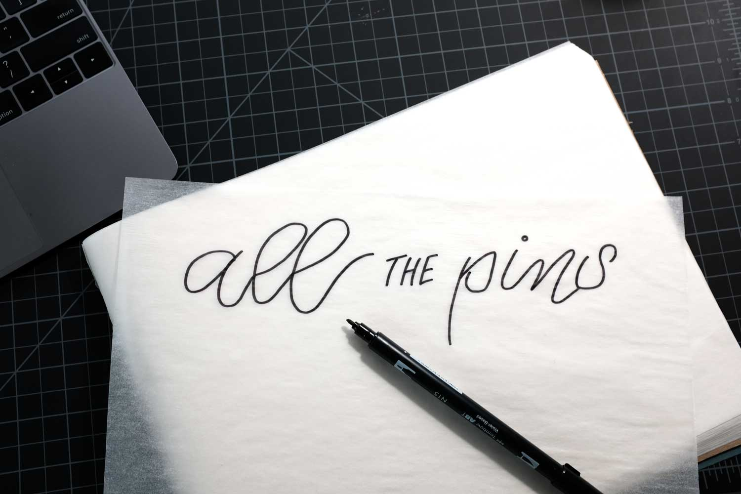 Hand lettered design on tracing paper for transfer to black felt