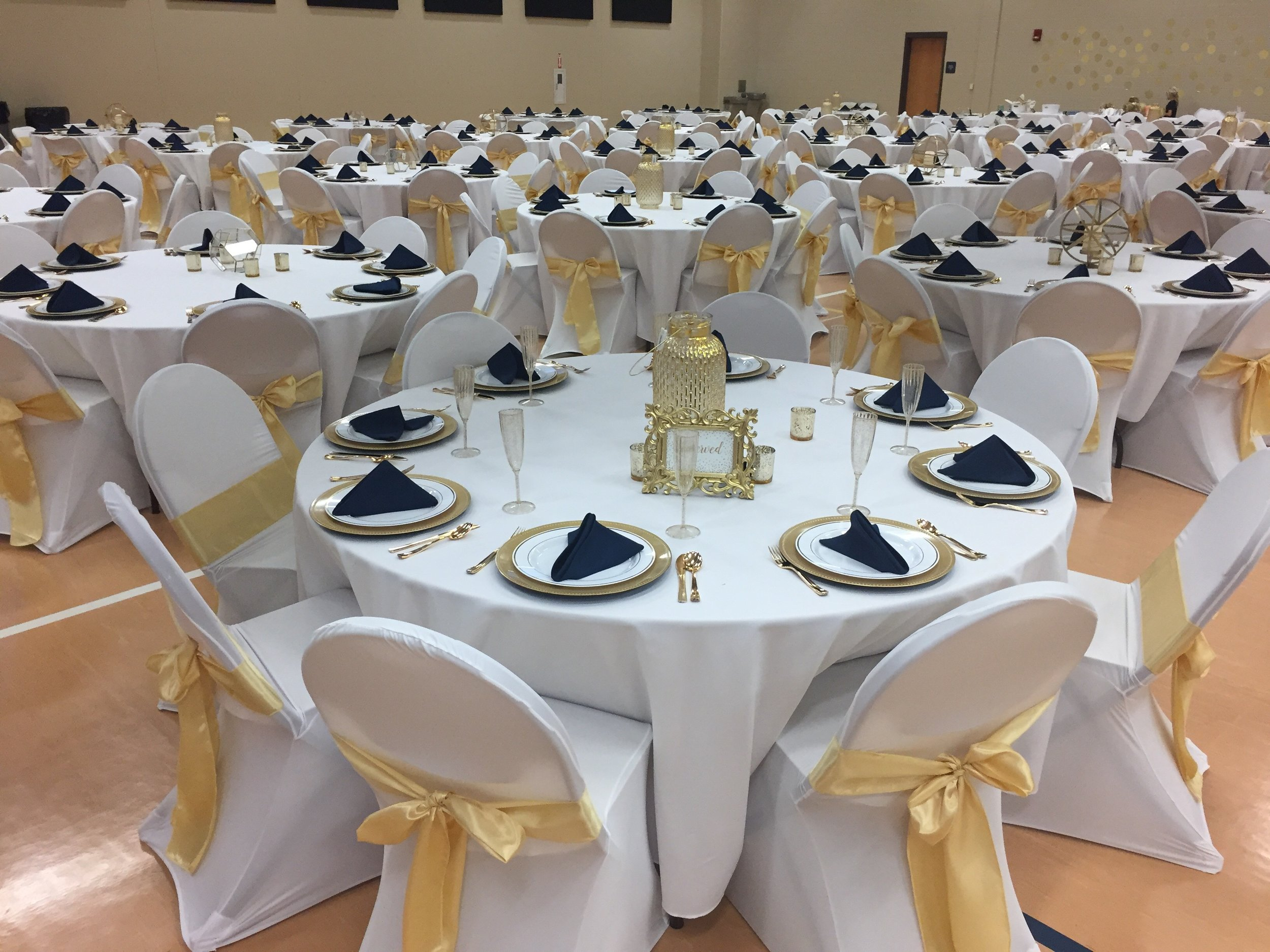 Butter yellow sashes with  white chair covers and gold chargers