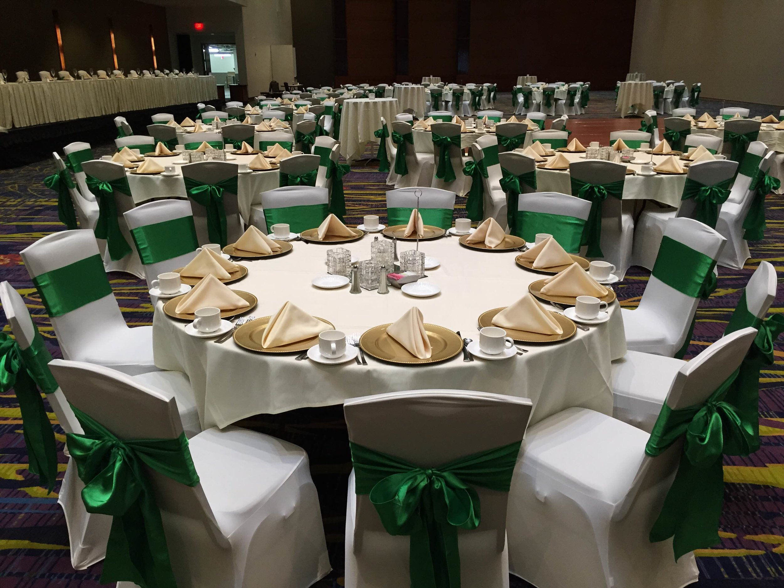 Green sashes, gold chargers, and white chair covers