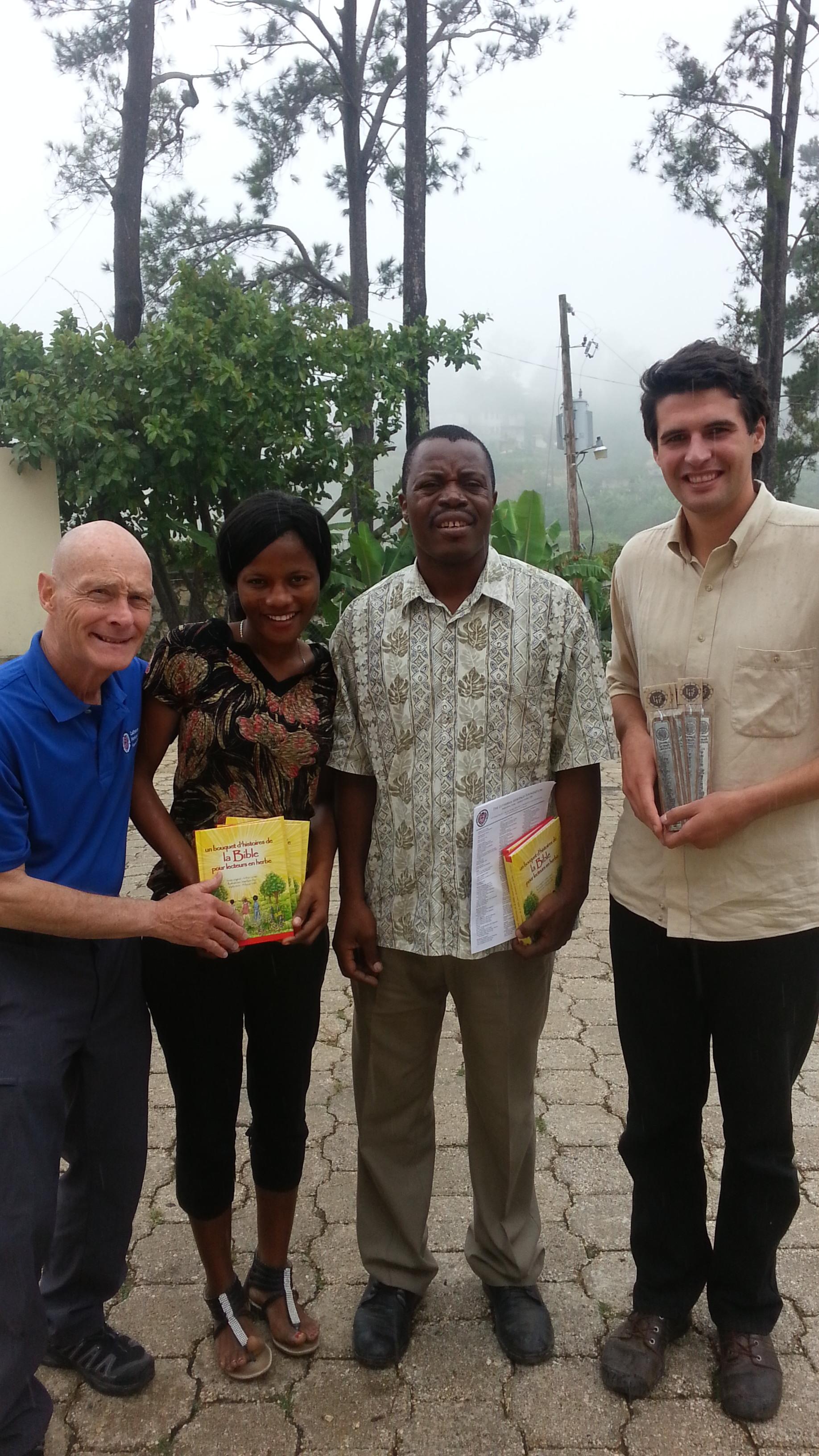 Photo of Rev. Larry Rockemann, Elaine, Rev. Daniel Paul and Ben Wiseman, NEHLM Liaison receiving picture story Bibles.