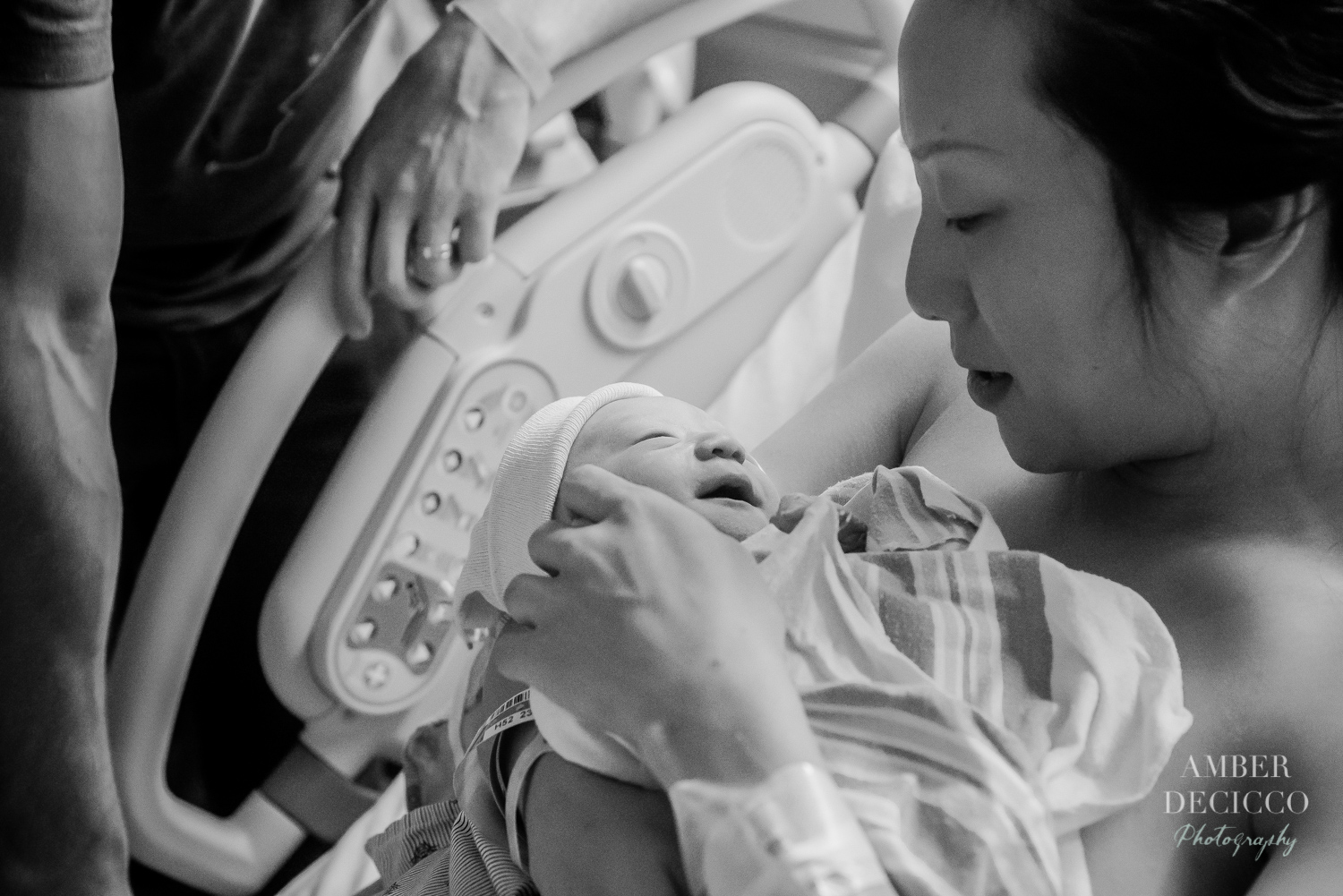 Mom and dad admiring their baby | Birth Photography ©Amber DeCicco Photography