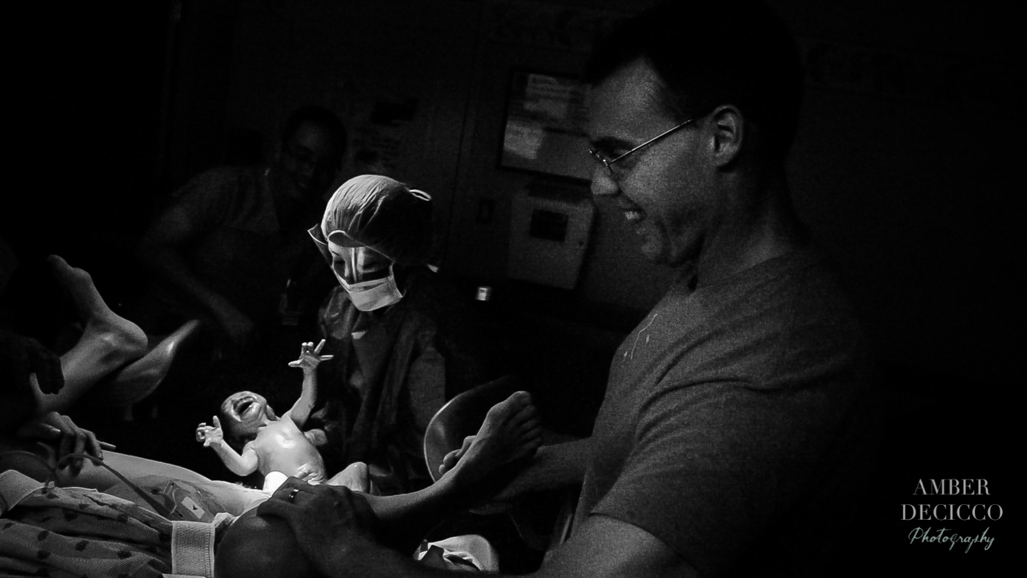 Dad is so happy when he sees his baby for the first time | Birth Photography ©Amber DeCicco Photography