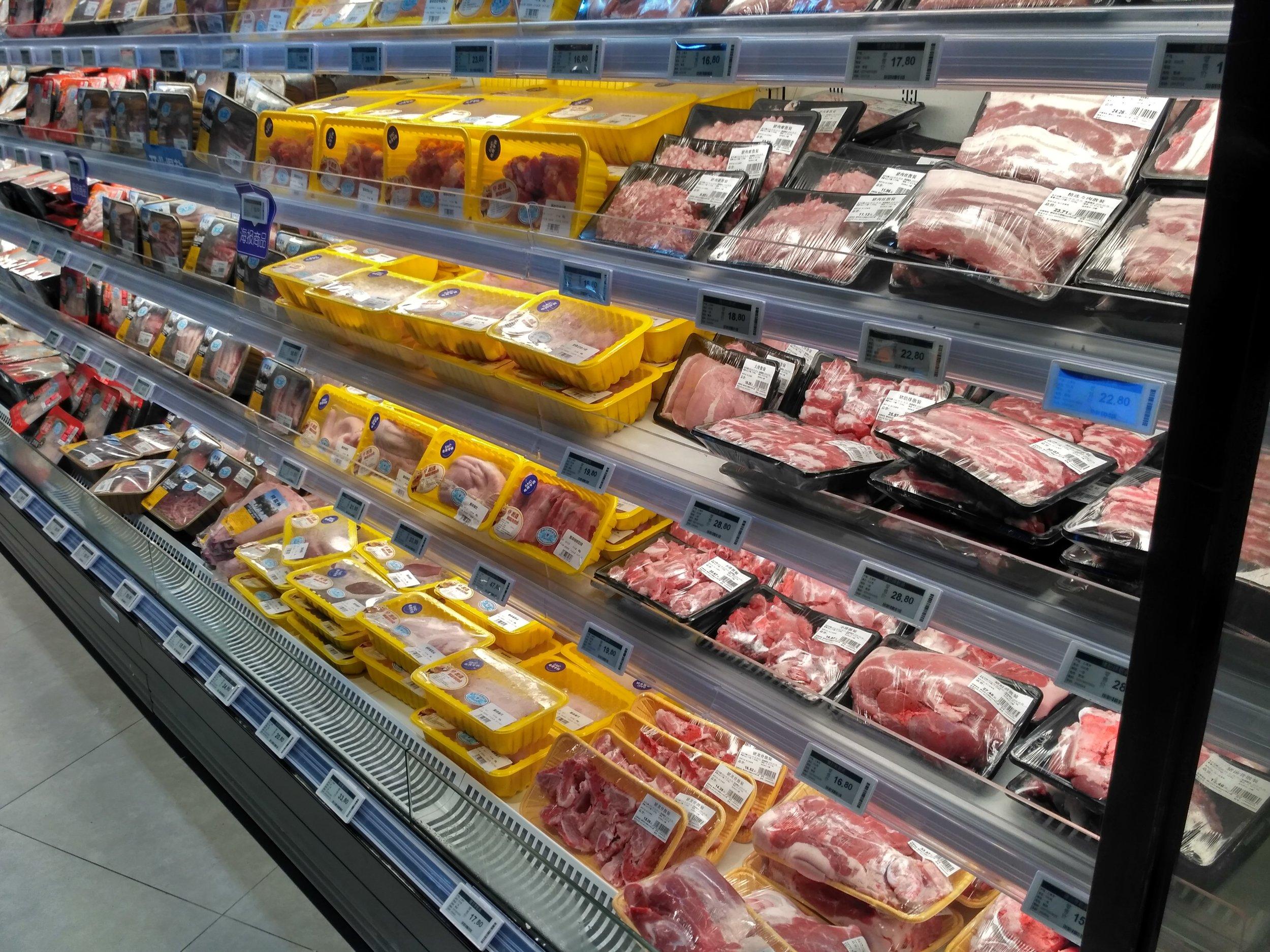 Digital price labels on fresh meat fridge shelves