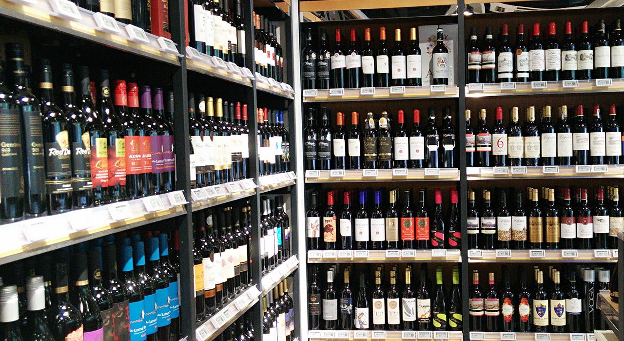 Digital price tags on shelf railings in a bottle shop