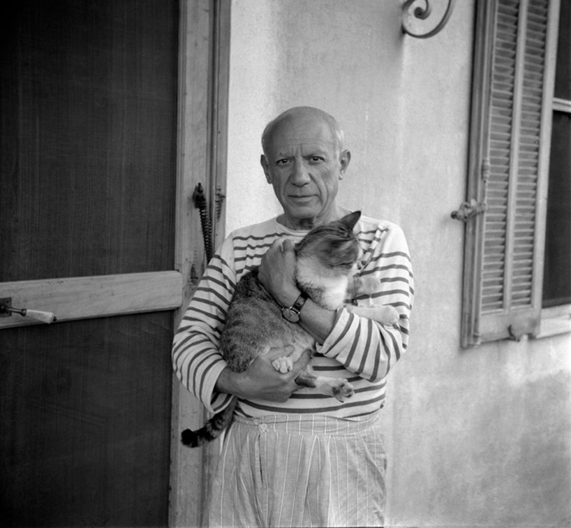 Pablo Picasso holding his cat.
