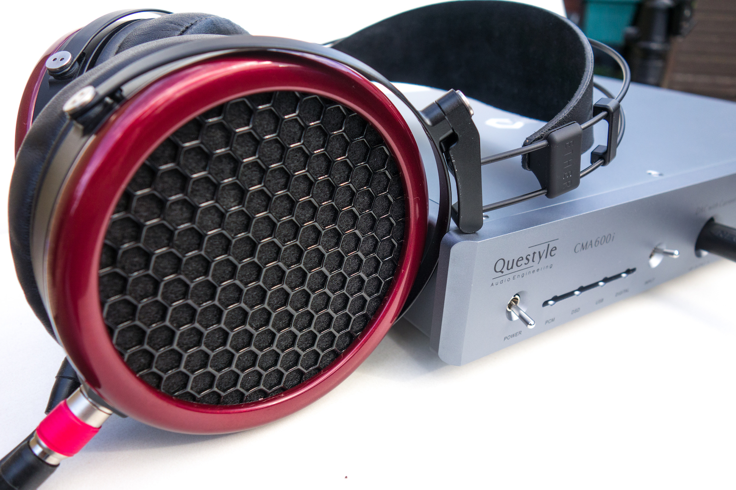 Side view of the Mr Speakers Ether headphones on top of the Questyle CMA600i headphone amp.