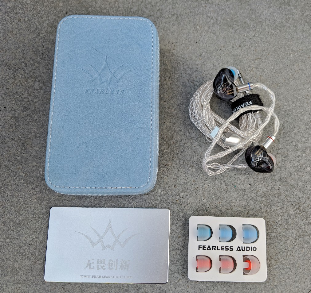 Fearless audio crystal pear and accessories. The earbuds come with a metal warranty card, some eartips and a blue leather carry case.