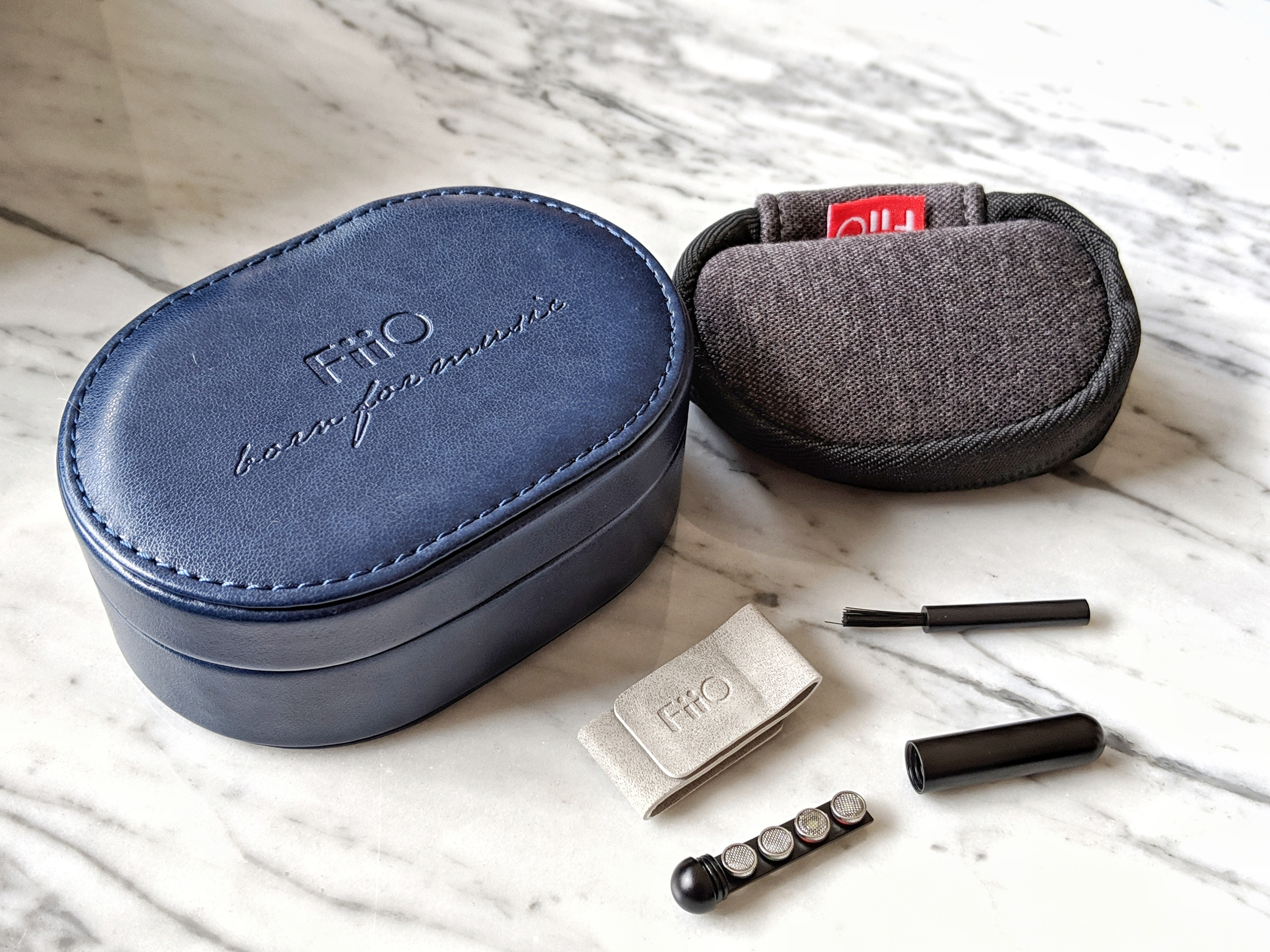 Fiio FH7 accessories including 2 cases, a cleaning tool, spare sound filers and a cable tidy.
