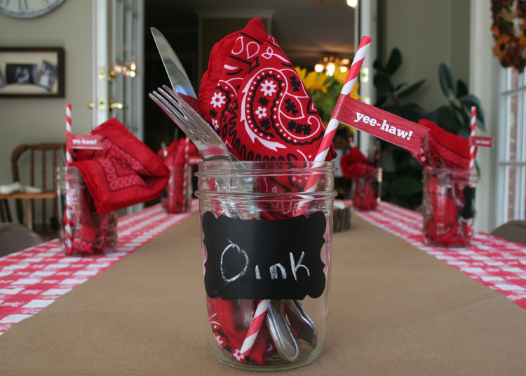 The tables were set with red and white checkered cloths and brown kraft paper. Mason jars containing bandana napkins, silverware and cutsie straws with pennants were at each place setting.