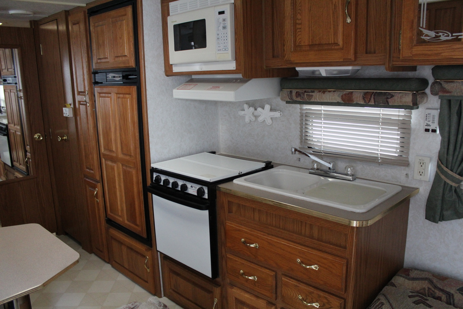 The kitchen has a decent fridge, an oven that can actually fit a chicken roaster in it (more unusual than you'd think in the small trailers) and enough storage spaces to survive. Just no counter top, unless you count the top of the stove. It will be cozy!